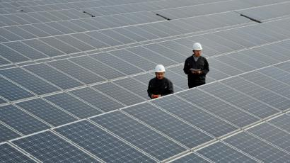 Chinese inspectors check arrays of solar panels at a photovoltaic power plant in Xiji town, Zaozhuang city, east Chinas Shandong province.