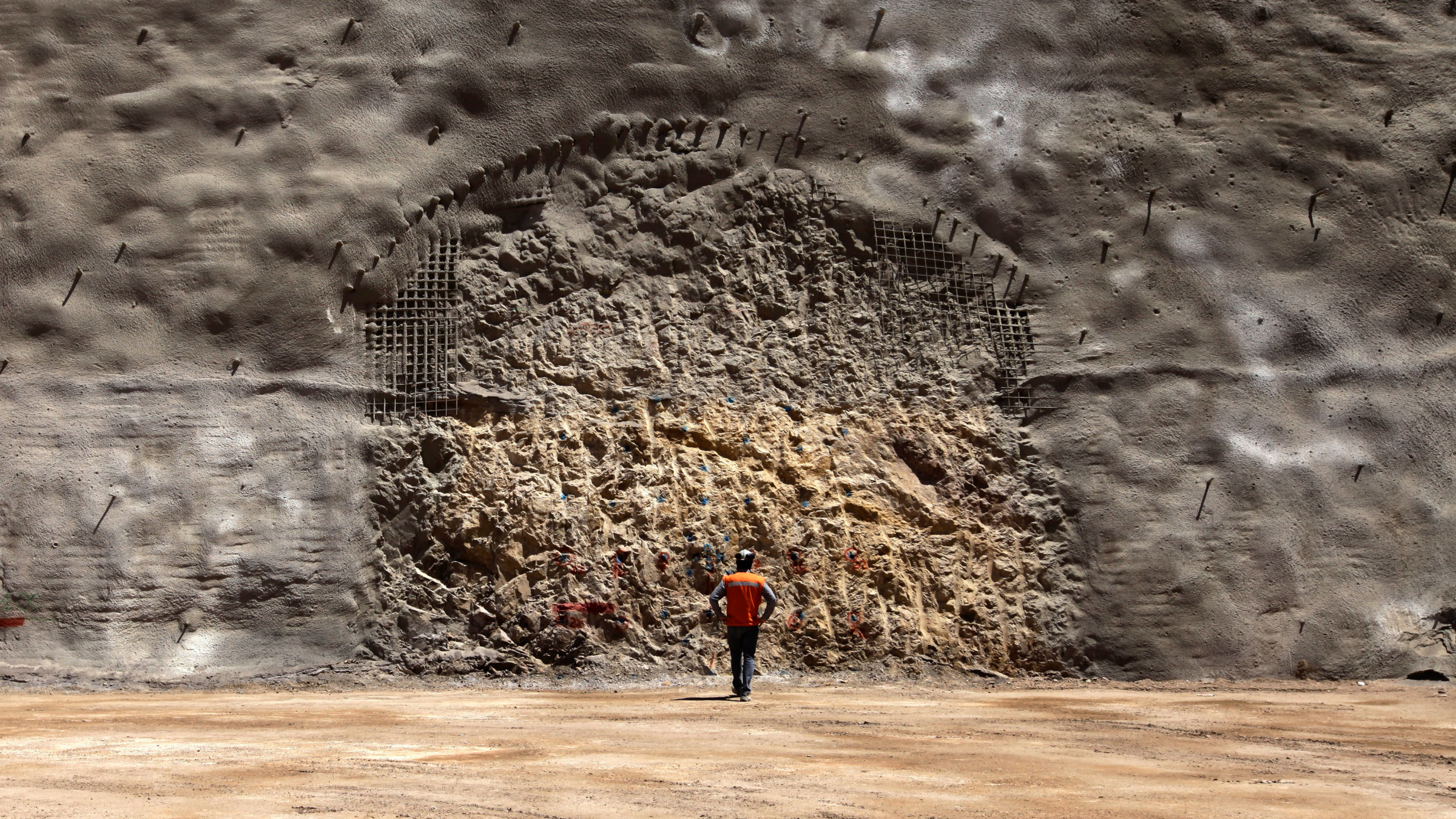 A worker from the National Copper Mine Corporation, or Codelco, looks at the area where a new tunnel is marked to be drilled at the Chuquicamata copper mine in the Atacama desert in northern Chile.