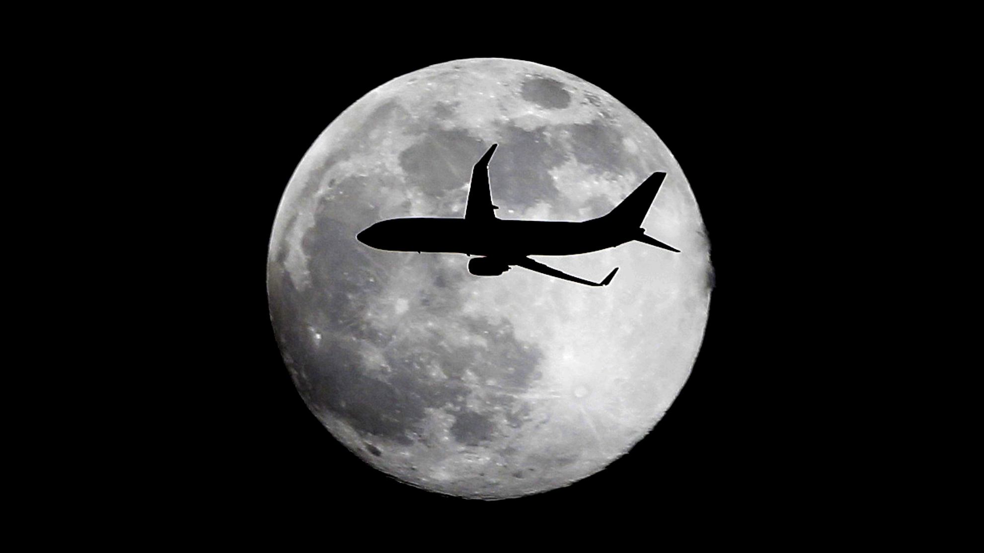 A jet plane leaving Miami International Airport flies in front of the moon, Saturday, June 22, 2013 above the skies in Surfside, Fla. The biggest and brightest full moon of the year graces the sky early Sunday as our celestial neighbor swings closer to Earth than usual when the moon will come within 222,000 miles of Earth and turn full around 7:30 a.m. EDT. (AP Photo/Wilfredo Lee)