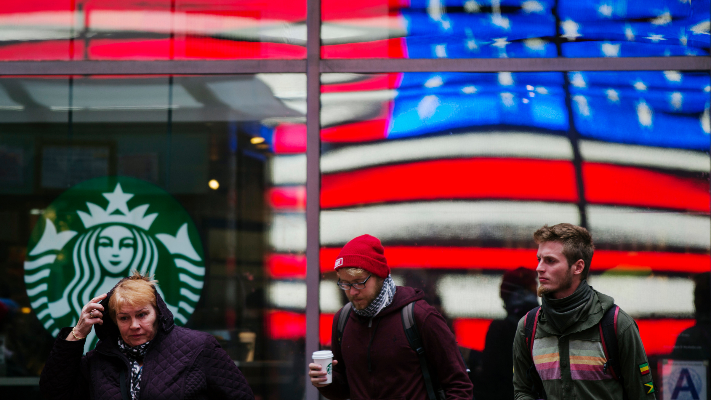 A woman pulls a hood over her head as she walks out of a Starbucks store into the cold wind at Times Square in New York.
