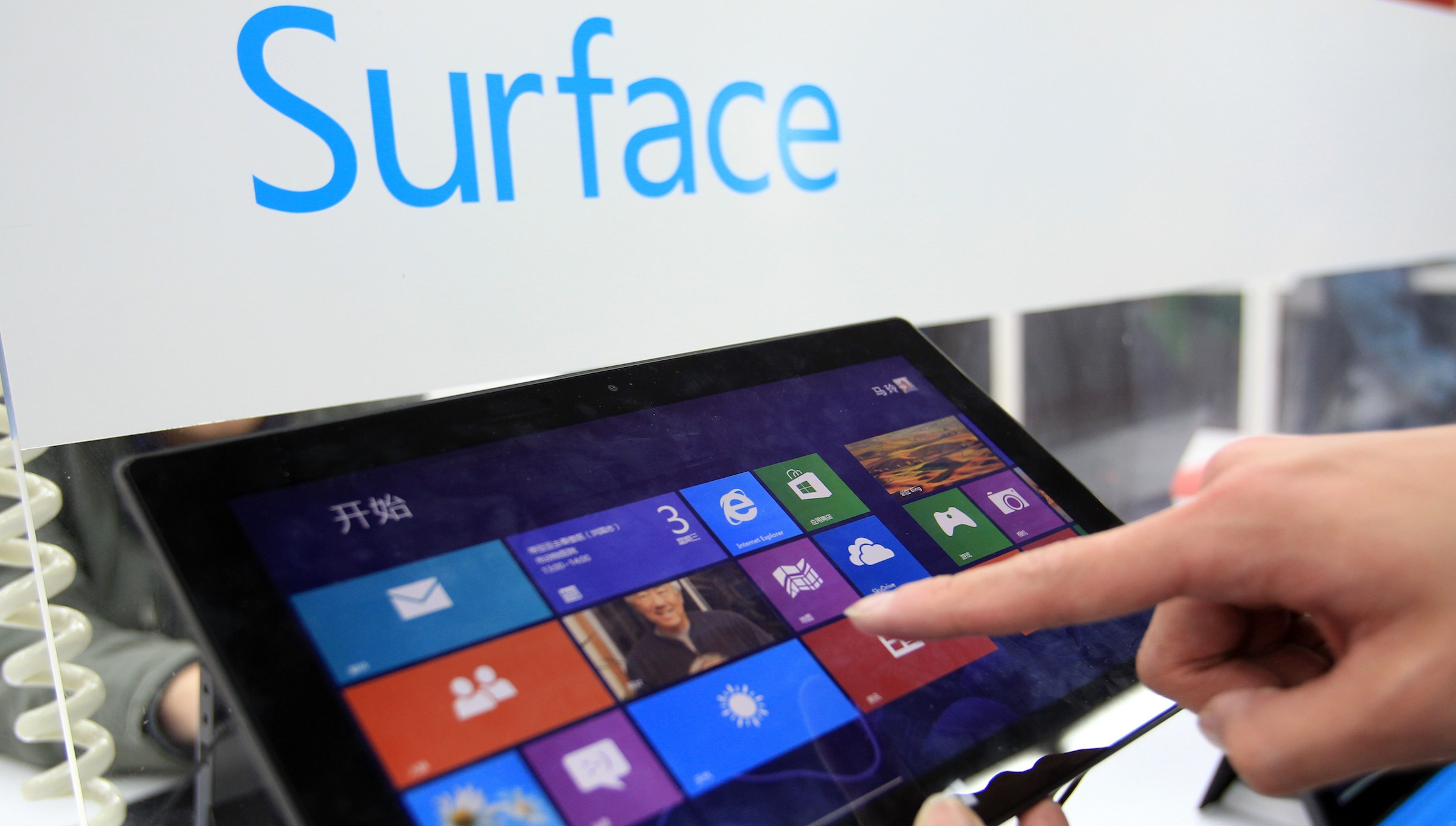--FILE--A Chinese shopper tries out a Microsoft Surface Pro tablet PC at a home appliances store in Shanghai, China, 3 April 2013.   Microsoft Corp.s after-sales service of its Surface tablet has attracted criticism from Chinas state-owned radio, following similar reports in the past month targeting Apple Inc. The Surface Pro should follow the nations law requiring notebook computers to have a one-year repair warranty for the whole device and a two-year warranty for main parts, as compared with the companys one-year pledge for both, China National Radio reported on Monday (8 April 2013). Joanna Li, a Beijing-based spokeswoman for Microsoft, said she couldnt immediately comment on the report today.