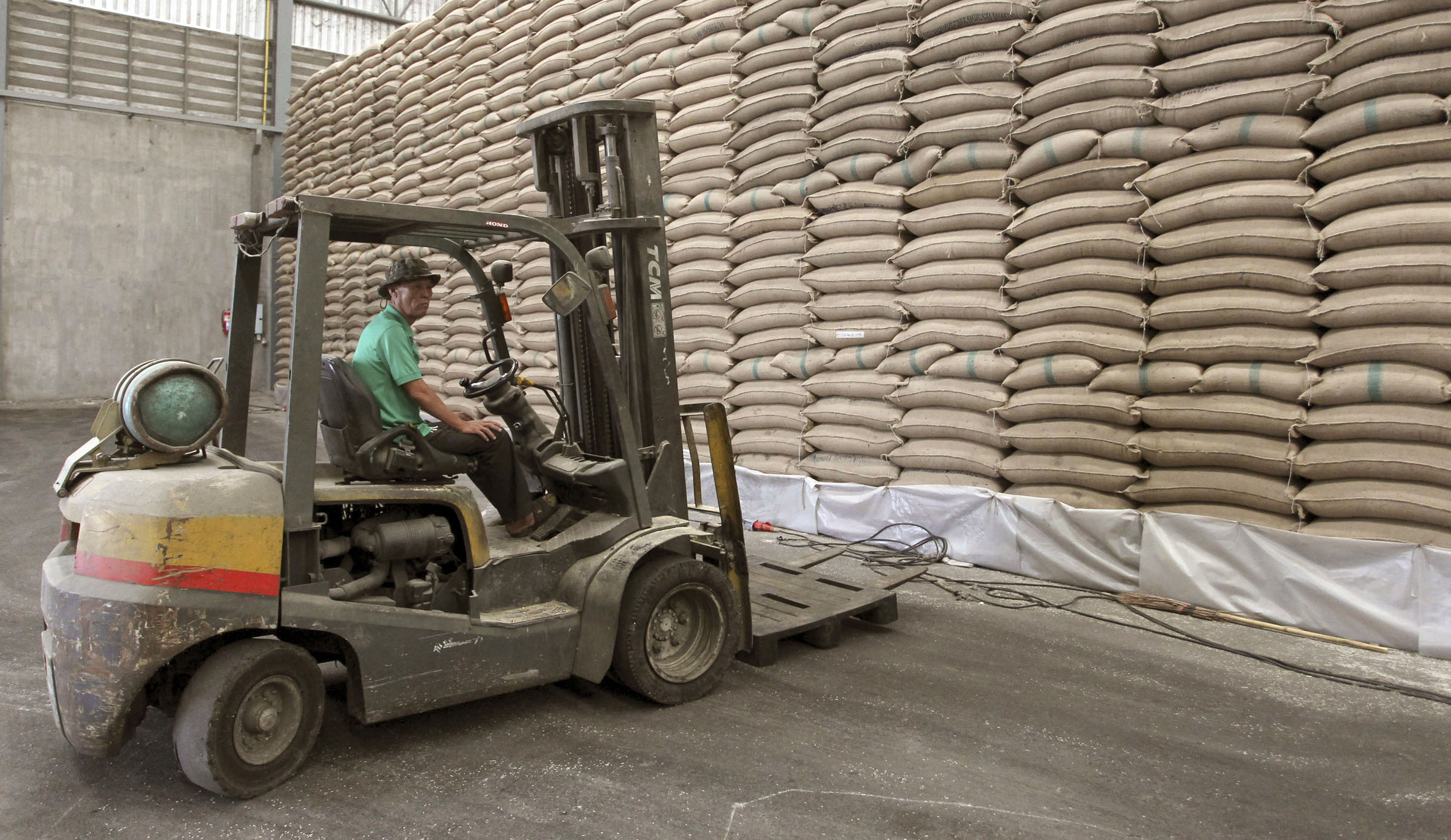 A worker loperates a forklift during an inspection of the rice stockpile at a warehouse Thursday, June 27, 2013, in Pathum Thani province, central Thailand. The Thai government said last week that it will pay farmers 12,000 baht ($389) per ton of rice, compared to the current price of 15,000 baht ($486), to reduce the losses from the 2011-12 subsidy program. The changes were in response to public criticism of the $4.4 billion loss incurred by the subsidy program, a flagship policy of Prime Minister Yingluck Shinawatra's government to win support from Thai farmers. (AP Photo/Apichart Weerawong)