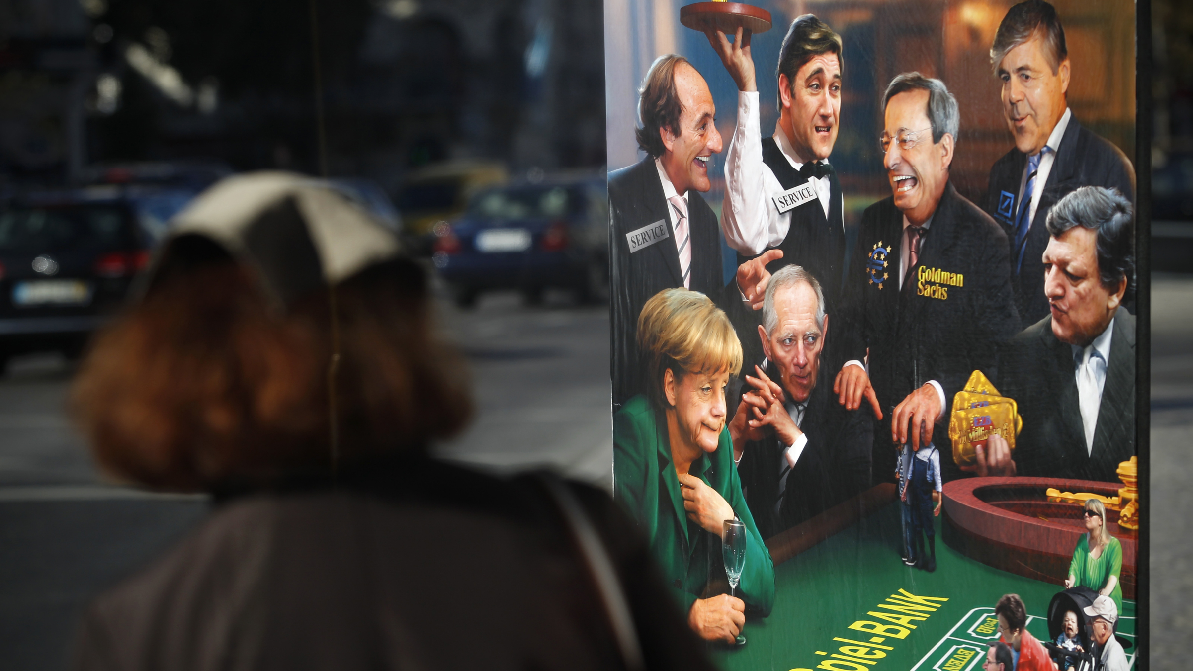 A woman looks at a board depicting Germany's Chancellor Angela Merkel, Portugal's Prime Minister Pedro Passos Coelho and Foreign Minister Paulo Portas, the President of the European Commission Jose Manuel Barroso, the President of the European Central Bank Mario Draghi, and the CEO of the Deutsche Bank Josef Ackermann gambling in a casino, in Lisbon, Tuesday, Nov. 13, 2012. Portuguese main union General Confederation of Portuguese Workers, CGTP, has called for a general strike on November 14, coinciding with similar work stoppages in Spain and Greece, to protest government-imposed austerity measures and labor reforms. The poster was put by a left wing politic party called Bloco Esquerda near a bus stop. (AP Photo/Francisco Seco)