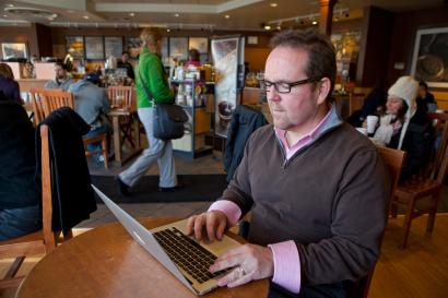 Ad salesman Tim Kilroy works remotely on his computer from a Starbucks