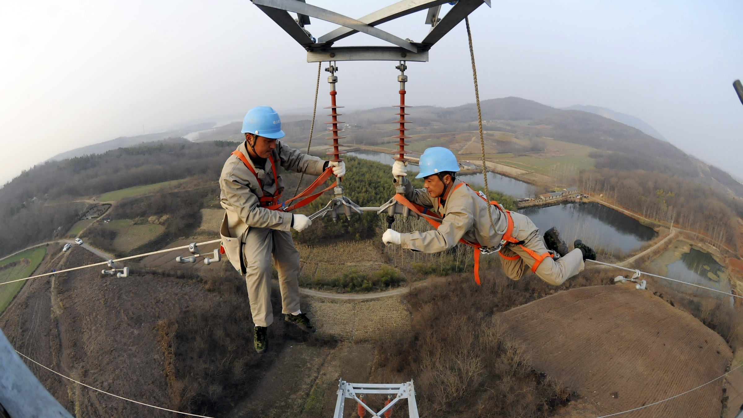 Workers check on electricity pylon situated amid farmlands in Chuzhou, Anhui province, February 5, 2013. A leading think tank of China predicted that China's GDP will grow in 2013 at a rate of 8.4 percent, up by 0.6 percentage points from that of 2012, Xinhua News Agency reported. REUTERS/China Daily