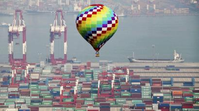 A hot-air balloon flies over a container port in Qingdao in east China's Shandong province Sunday, Sept. 9, 2012. Asia-Pacific leaders focused their attention on rising concern over food security on Sunday, as they prepared to wrap up their annual summit with an agreement to slash tariffs on trade in environmental goods and a call to keep markets open even in hard times. (AP Photo
