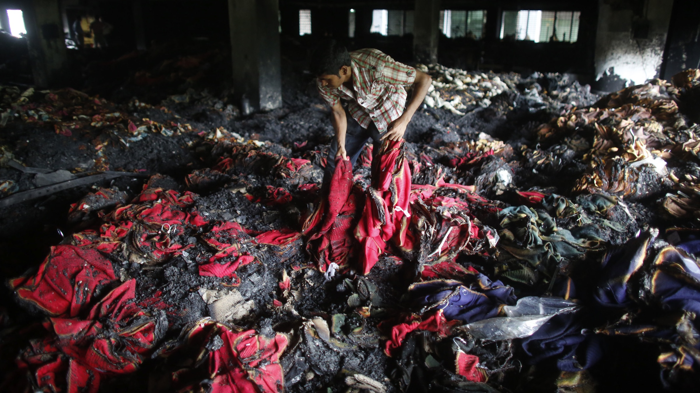 A garment worker inspects a factory belonging to Tung Hai Group, a large garment exporter, after a fire in Dhaka May 9, 2013. Eight people were killed when the fire swept through the garment factory in an industrial district of the Bangladeshi capital Dhaka, police and an industry association official said on Thursday. REUTERS/Andrew Biraj (BANGLADESH - Tags: DISASTER BUSINESS TEXTILE) - RTXZFV5