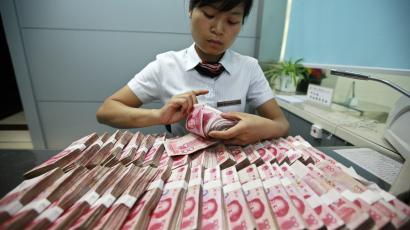 A bank clerk counts Chinese yuan banknotes at a branch of Industrial and Commercial Bank of China in Huaibei, Anhui province June 8, 2012. China's top five banks said on Friday they have raised deposit rates to 3.5 percent, above the benchmark level, less than a day after China took a step towards liberalising its interest rate market. REUTERS/Stringer