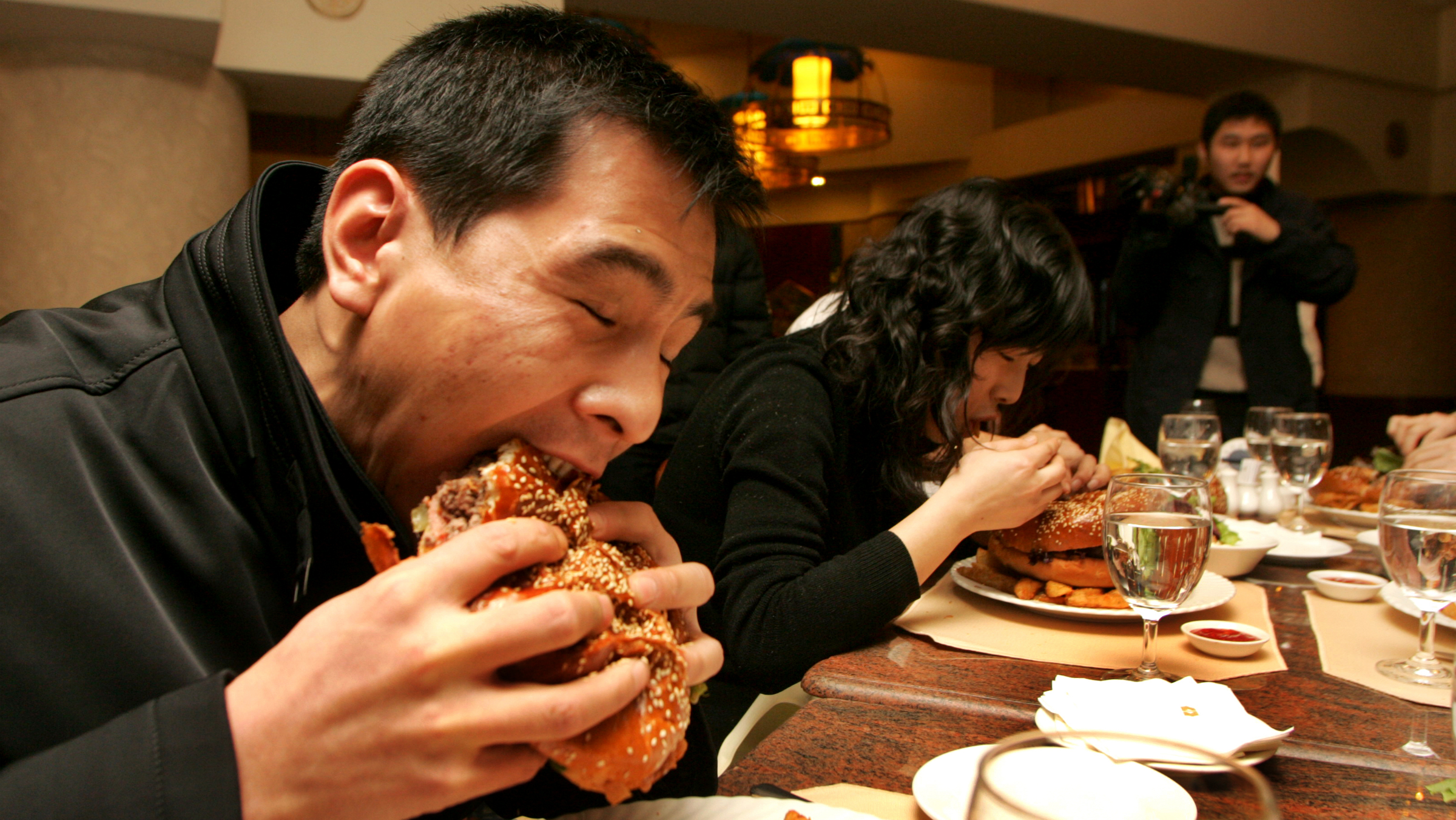 A Chinese man and a woman eat hamburger during a Burger King contest in XiAn, northwest Chinas Shaanxi province, January 22, 2007. Obesity levels in China are rising fast, with more than a quarter of the adult population overweight or obese, as people add more meat and dairy products to their diet, causing serious health problems, a new study says. Chinese people now derive a far larger proportion of energy from fat and animal-based foods, such as meat and eggs, compared with in the past, the study found. The change in diets and lifestyles, where Chinese less frequently have to engage in physical activity at work, is consequently leading to a rise in cancer and coronary heart disease. According to the study, the classical Chinese diet -- rich in vegetables and carbohydrates with minimal animal-sourced food -- no longer exists.(Imaginechina via AP Images