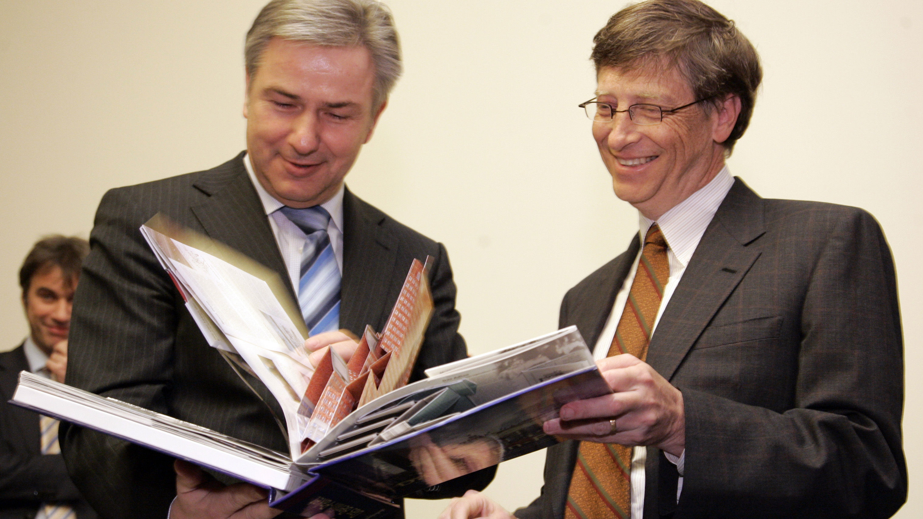 Berlin mayor Klaus Wowereit, left, and Microsoft founder Bill Gates, right, take a look at book about Berlin after Gates signed the Golden guest book of the City of Berlin in the Red City Hall in Berlin on Tuesday, Jan. 22, 2008. (AP Photo/Miguel Villagran)