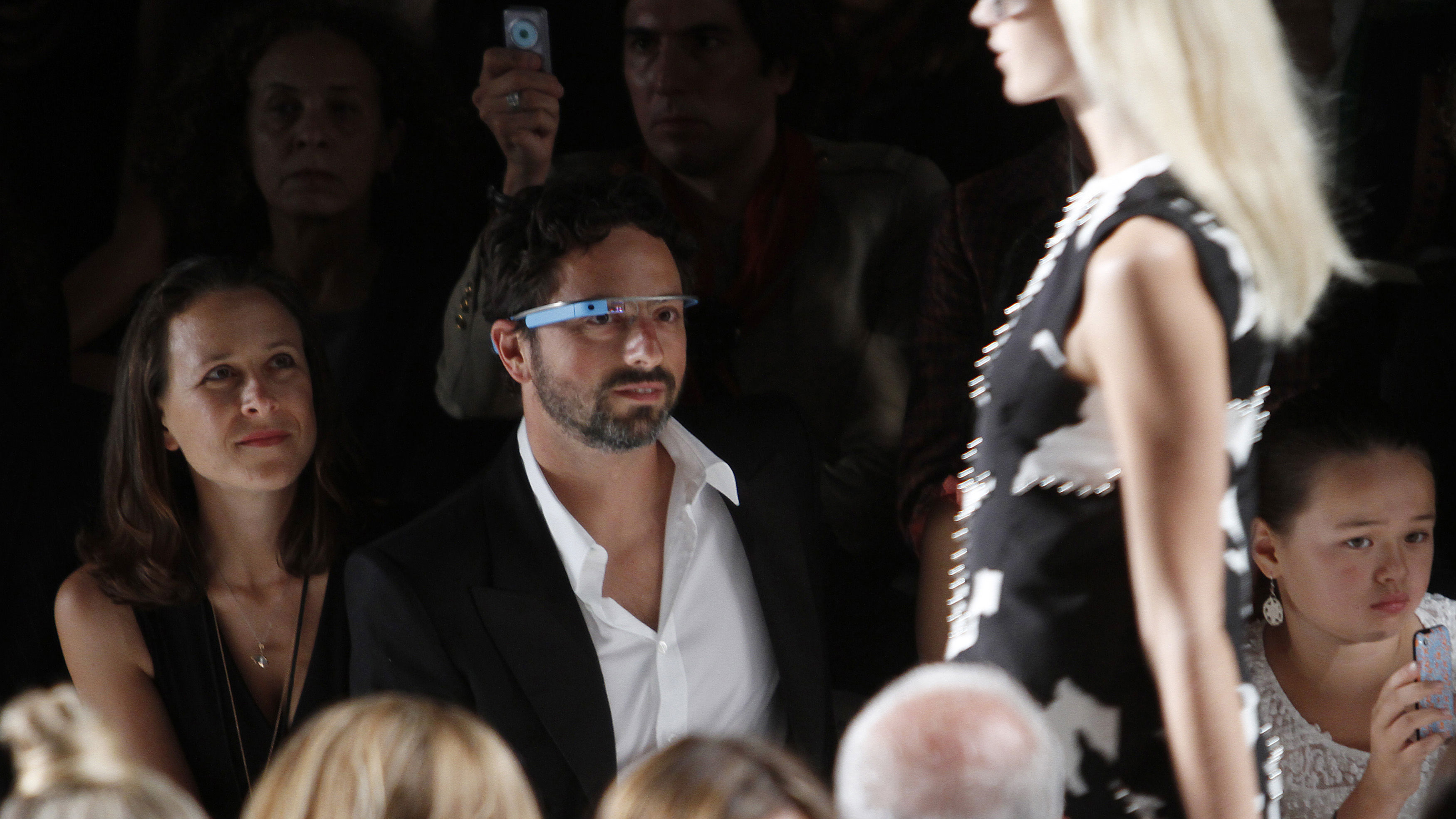"""Google founder Sergey Brin (R) and a guest watch the the Diane von Furstenberg Spring/Summer 2013 collection show during New York Fashion Week September 9, 2012. The show was used as a launching event for Google's new product """"Glass by Google"""". REUTERS/Carlo Allegri"""