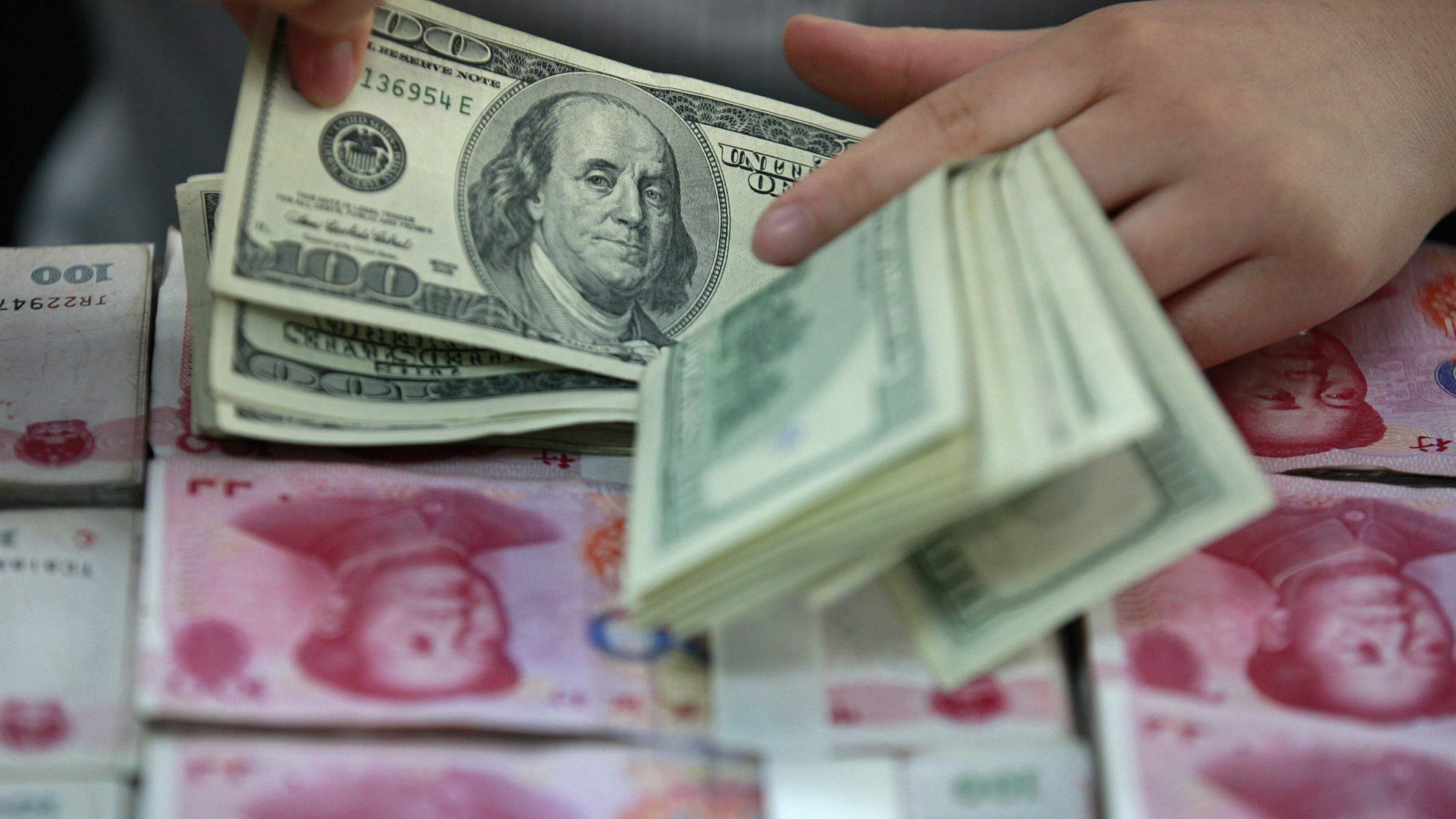 A bank clerk counts U.S. dollar banknotes on bundles of 100 Chinese yuan banknotes at a branch of a bank in Huaibei, Anhui province April 26, 2012. China is likely to follow up its decision to widen the trading band for its renminbi currency with more steps to let market forces set exchange rates, People's Bank of China Deputy Governor Yi Gang said on Saturday. REUTERS/Stringer