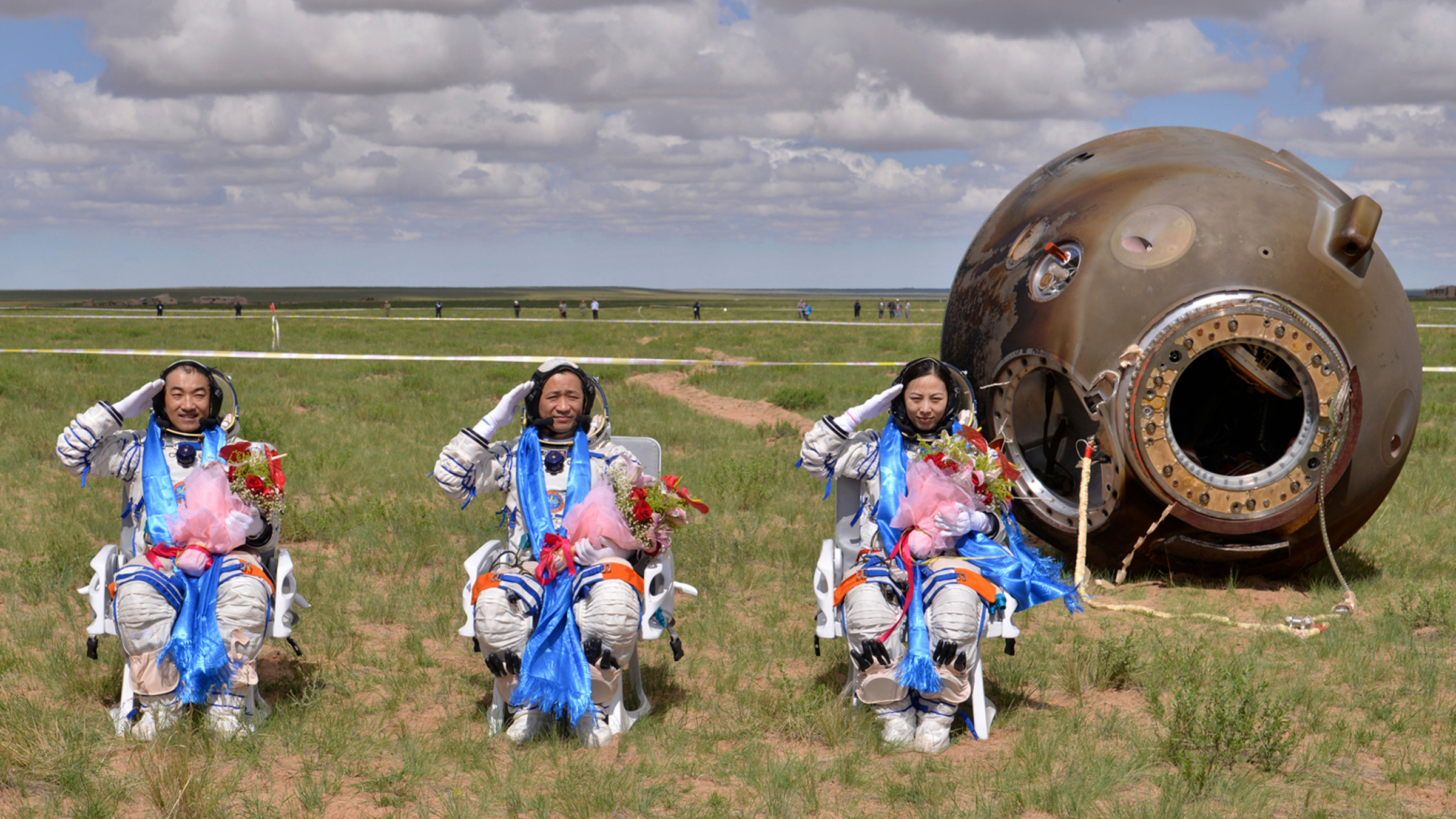 Astronauts (L-R) Zhang Xiaoguang, Nie Haisheng and Wang Yaping salute after returning to earth in the re-entry capsule of China's Shenzhou-10 spacecraft.