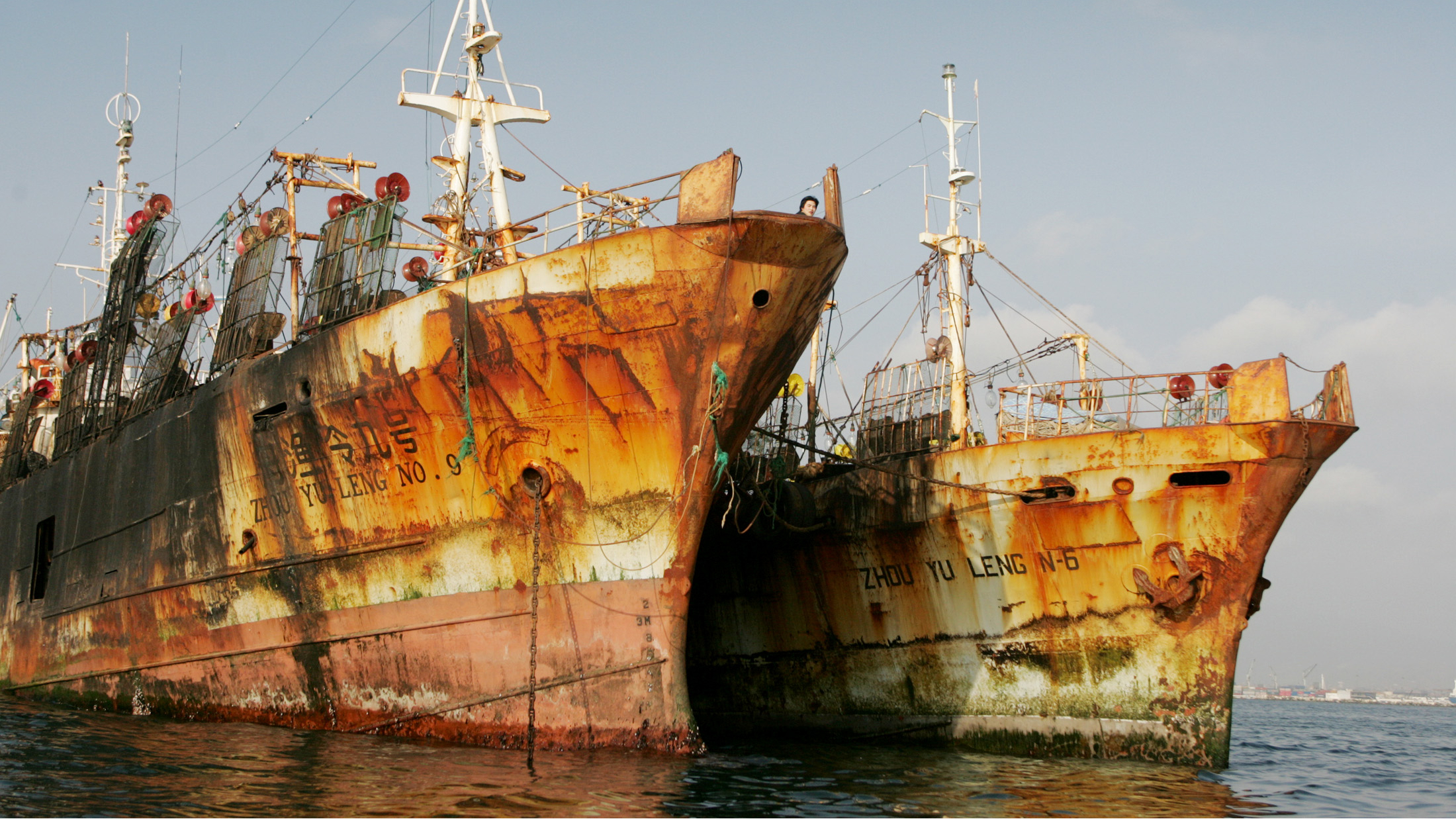 Two of the nine Chinese vessels caught by Peruvian navy are anchored in the port of Callao, November 24, 2004. Peruvian authorities seized nine Chinese vessels on November 19, allegedly fishing illegally six miles within Peru's territorial waters. The fleet was seized and escorted to the port of Callao in Lima. 192 crewmembers will remain on board arrested vessels until investigations are concluded. REUTERS/Mariana Bazo MB