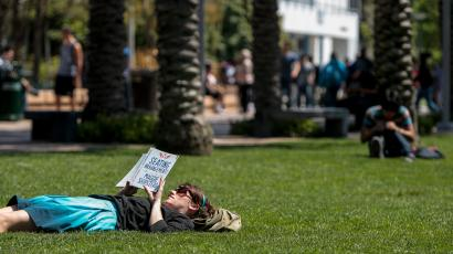 Santa Monica College English Department Assistant Ginger Pennington reads a book while lying on the lawn at Santa Monica College in Santa Monica, California April 4, 2012. The president of the California college defended on Wednesday the use of pepper spray by campus police against students protesting higher tuition for extra summer-school classes, an incident that left as many as 30 people overcome by the caustic substance.
