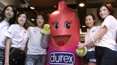 Models pose with a replica of a condom during the 2001 Durex Global Sex Survey Press conference in Hong Kong November 27, 2001. Durex SSL International said on Tuesday that its annual poll of 18,500 people in 28 countries showed the world was having more sex and starting earlier than ever before, and the United States was leading the field in all departments. Results showed Americans averaged sex 124 times a year with over 14 different partners, making the United States the world's sexual superpower. REUTERS/Kin Cheung