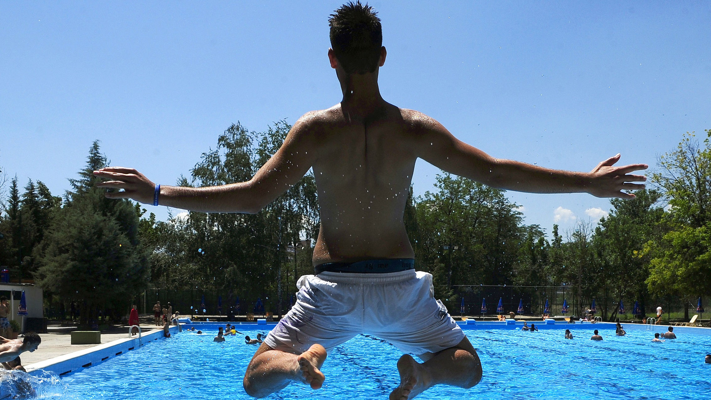 A man jumps into a swimming pool.