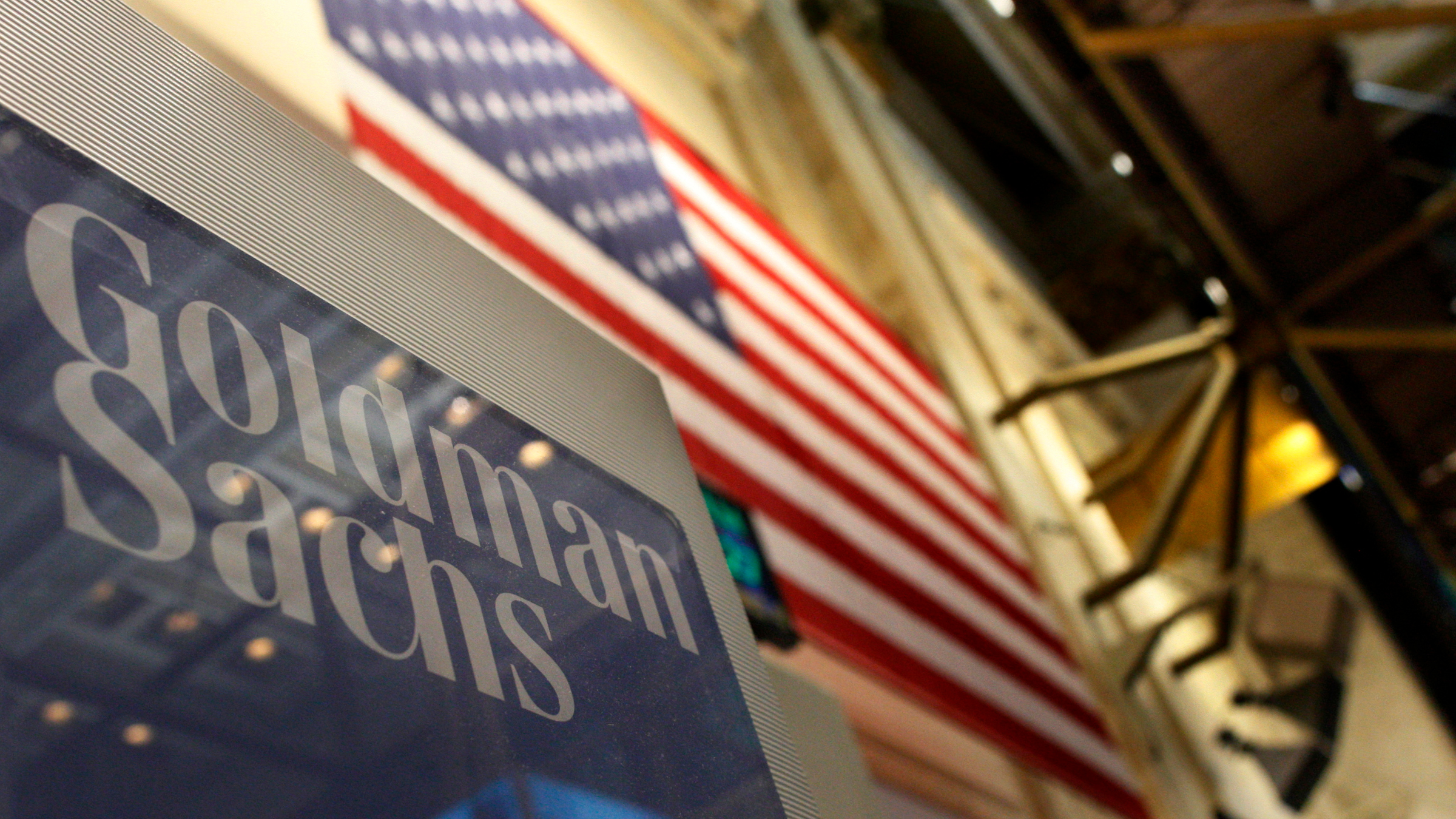 Goldman Sachs logo next to an American flag.