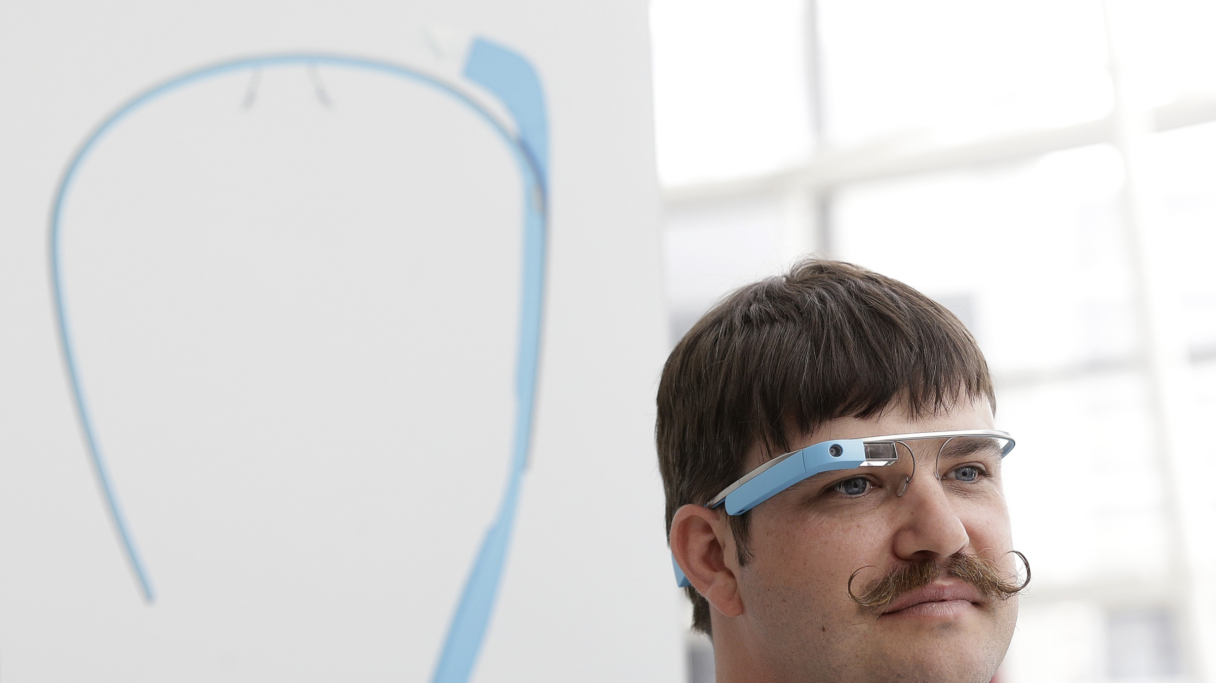 Engineer Ian McKellar wears a pair of Google Glass at a booth at Google I/O 2013 in San Francisco, Wednesday, May 15, 2013. (AP Photo/Jeff Chiu)