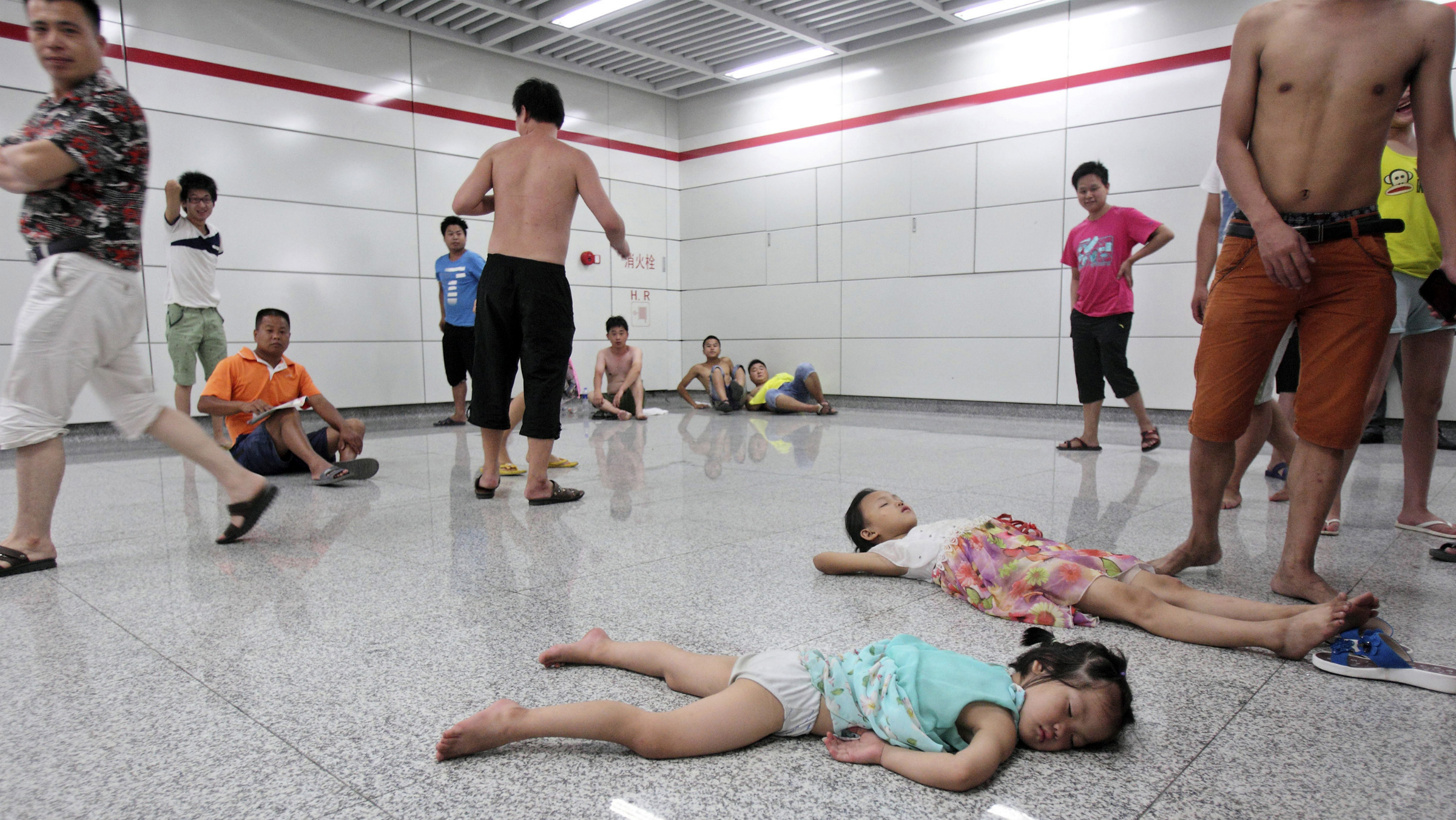 Children sleep on the floor of the Qiaosi subway station in Hangzhou, Zhejiang province July 25, 2013. More than 600 people cooled off inside the subway station as temperatures in the city hit a high of 40 degrees Centigrade during a regional power outage on Thursday. Picture taken July 25, 2013. REUTERS/Stringer