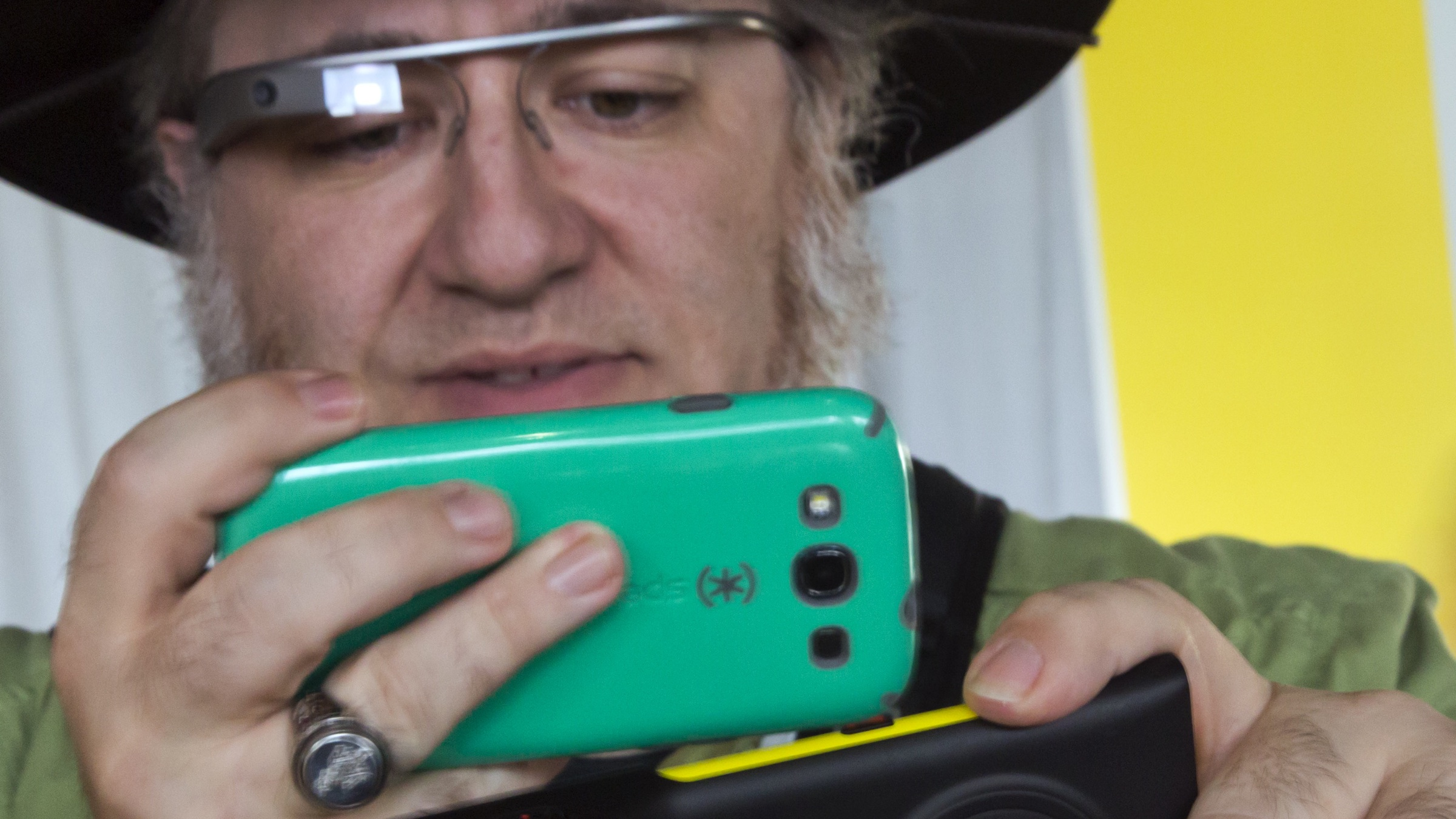 Journalist Andy Inahtko, from Chicago, wearing Google Glass, uses a smartphone to photograph a Nokia Lumia 1020 at its introduction,  in New York,  Thursday, July 11, 2013. The Nokia Lumia 1020, with a 41-megapixel camera, records more detail than other camera phones and even tops point-and-shoot cameras. (AP Photo/Richard Drew)