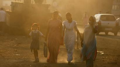 People walk through haze at an industrial area in Mumbai December 3, 2009. India will not accept a legally binding emission cut nor a peak year of carbon emissions at the global climate talks in Copenhagen, Environment Minister Jairam Ramesh said on Thursday. REUTERS/Arko Datta
