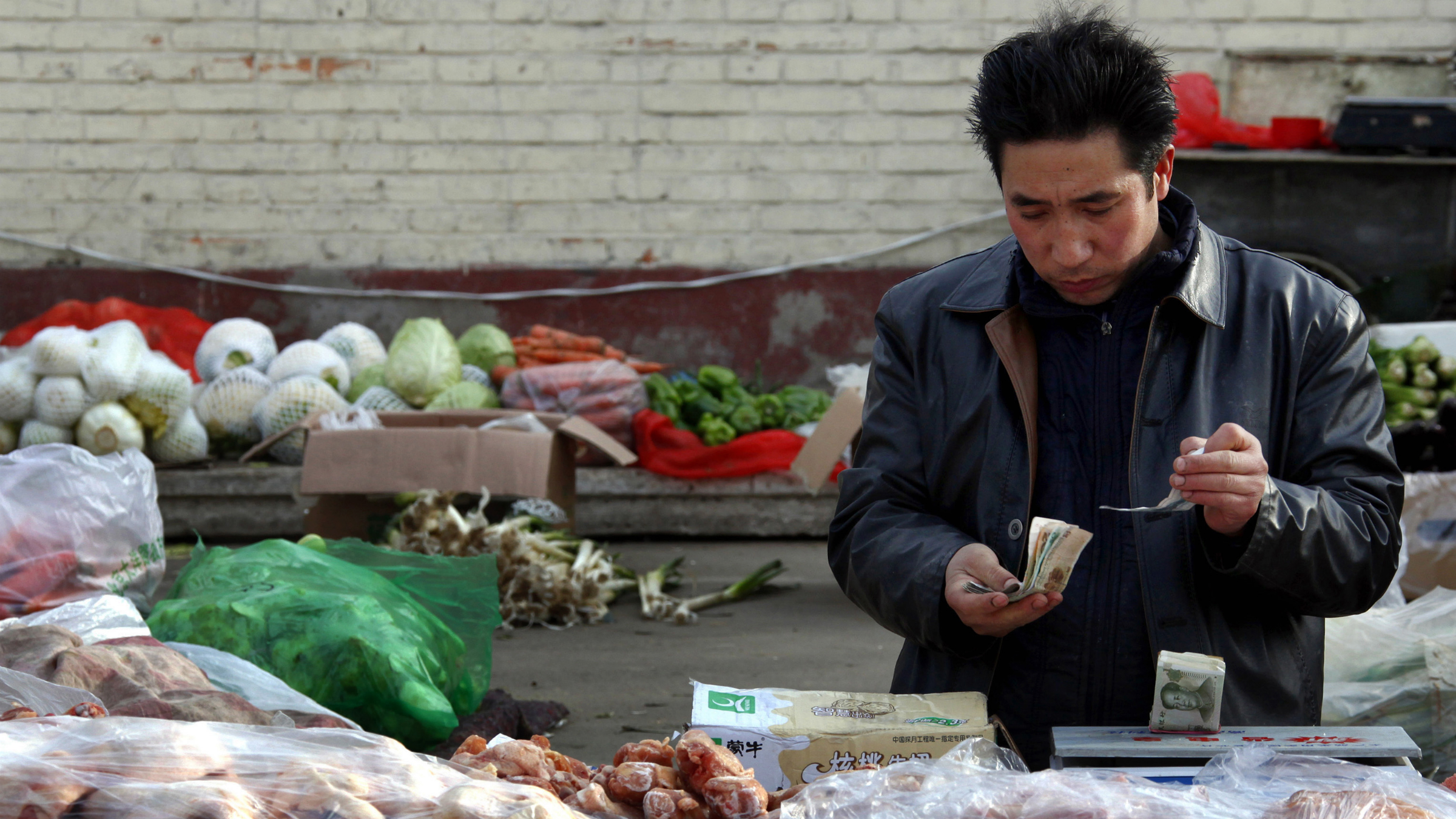 Fruit and vegetables can be seen behind a man selling pork as he checks his money at a small roadside market in central Beijing March 1, 2011. China's annual consumer price index (CPI) may reach 4.5 percent in the first quarter and peak this year in the second quarter, the official Shanghai Securities News on Monday quoted a research report as saying. In one sign of the accumulating pressures, core inflation, stripped of volatile food prices, jumped to 2.6 percent year on year, the highest in at least a decade, from 2.1 percent a month earlier. REUTERS/David Gray