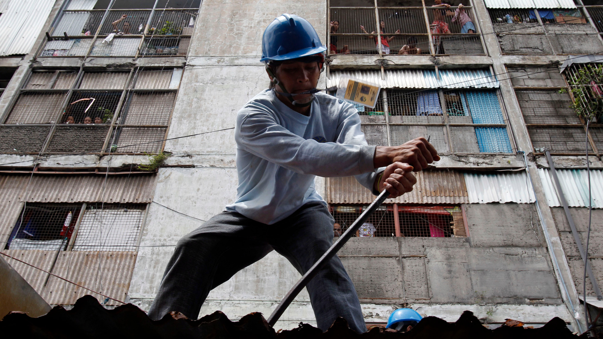 A member of the government demolition team removes the roof of a condemned structure in Vitas, Tondo city, metro Manila June 14, 2011. Manila city's government has been removing people from the dilapidated structures (in background) to avoid deaths in case of earthquake or accidents. At least hundreds of families were occupying the condemned dilapidated structures.