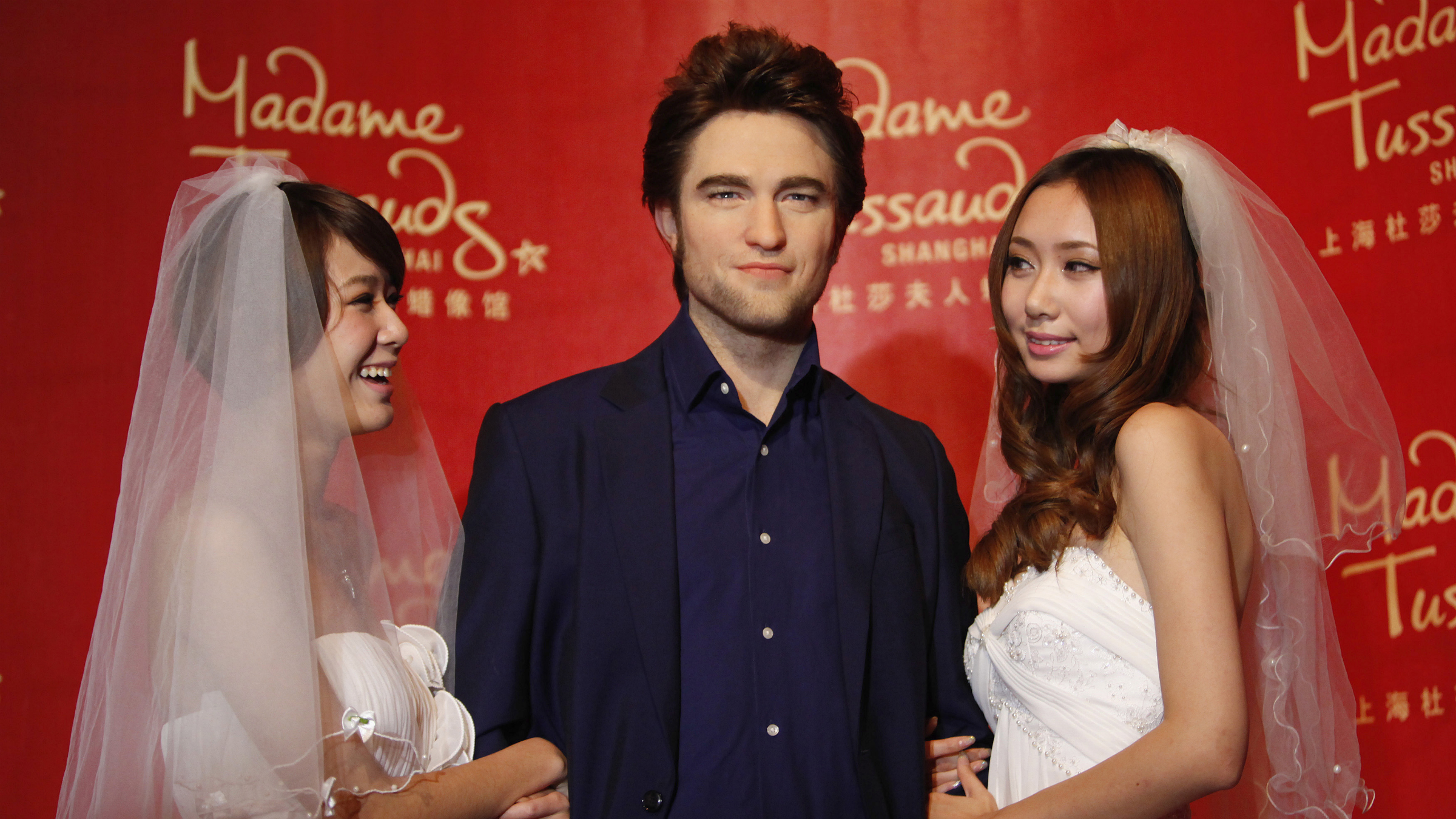 Models pose next to a wax statue of actor Robert Pattinson (C) at the Madame Tussauds Wax Museum in Shanghai December 1, 2011. REUTERS/Aly Song