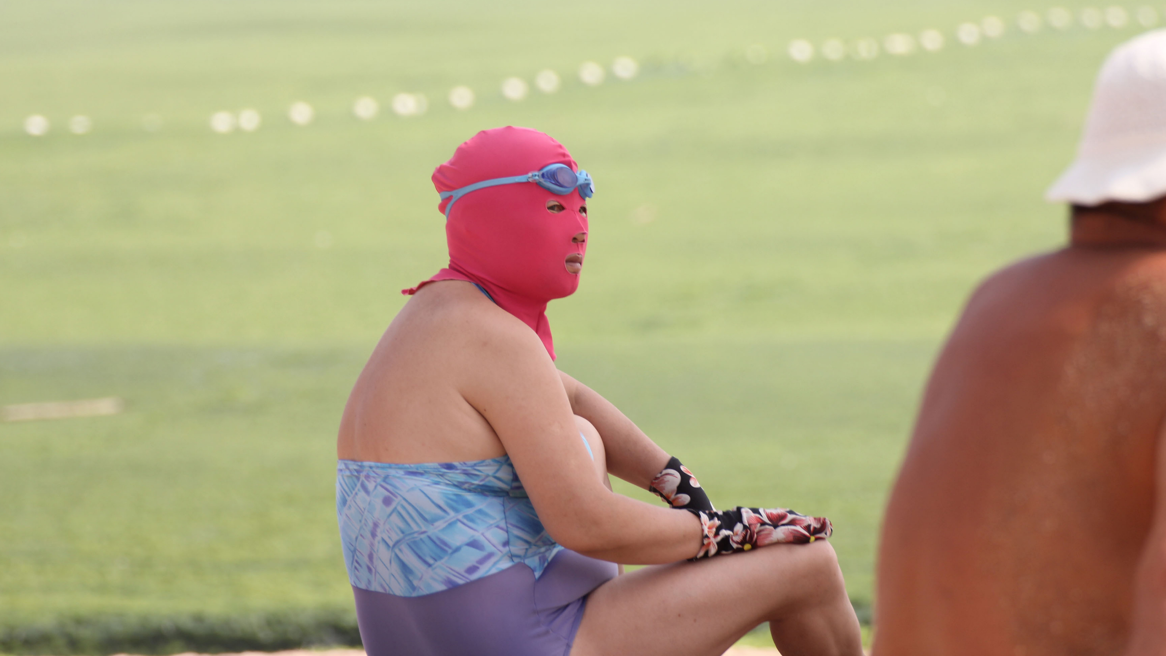 A masked female holidaymaker looks on at a beach resort on a scorching day in Qingdao city, east Chinas Shandong province, 3 July 2013. Holidaymakers are flooding to the beach resorts to cool down in the eastern Chinese coastal city of Qingdao as heat waves are sweeping through many parts of China. A group of female swimmers are spotlighted among the others as they dress their heads up with colorful masks, making them look like masked robbers or terrorists. Dubbed as the bikini for faces, the mask is used to protect the face of its user from being tanned by scorching sunlight and stung by jellyfish. Priced at 15-20 yuan (US$2.44-US$3.26) apiece, the mask is quite popular among middle-aged and elderly women.(Imaginechina via AP Images