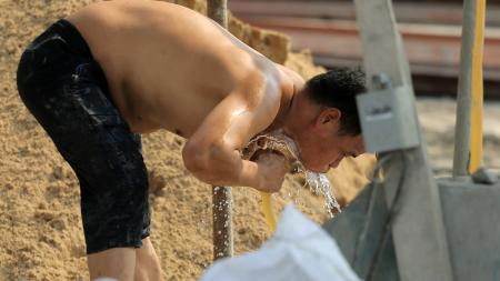 A Chinese migrant worker hoses water on his body to cool down at a construction site on a scorching day in Shanghai, China, 10 July 2013. No relief from the heat is expected for at least five days in Shanghai with a high of 37 degrees Celsius and lots of sun forecast on Thursday (18 July 2013). Friday will also be sunny and the high hits 38 degrees as the heat wave will continue through the weekend, the Shanghai Meteorological Bureau said. On Wednesday, the high reached 35.4 degrees. It was the 13th high temperature day of 35 degrees or above this month. According to the weather bureau, it was the second longest period for high temperature days since records started being kept in 1873. In 1934, 16 high temperature days were recorded on July 1-17. Wednesday also marked the 15th high temperature day this summer, the bureau said.(Imaginechina via AP Images