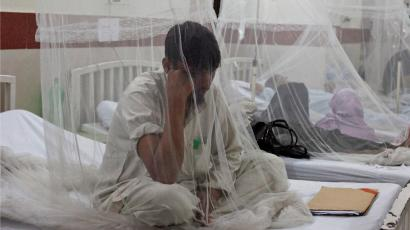 A man sitting under a mosquito net.
