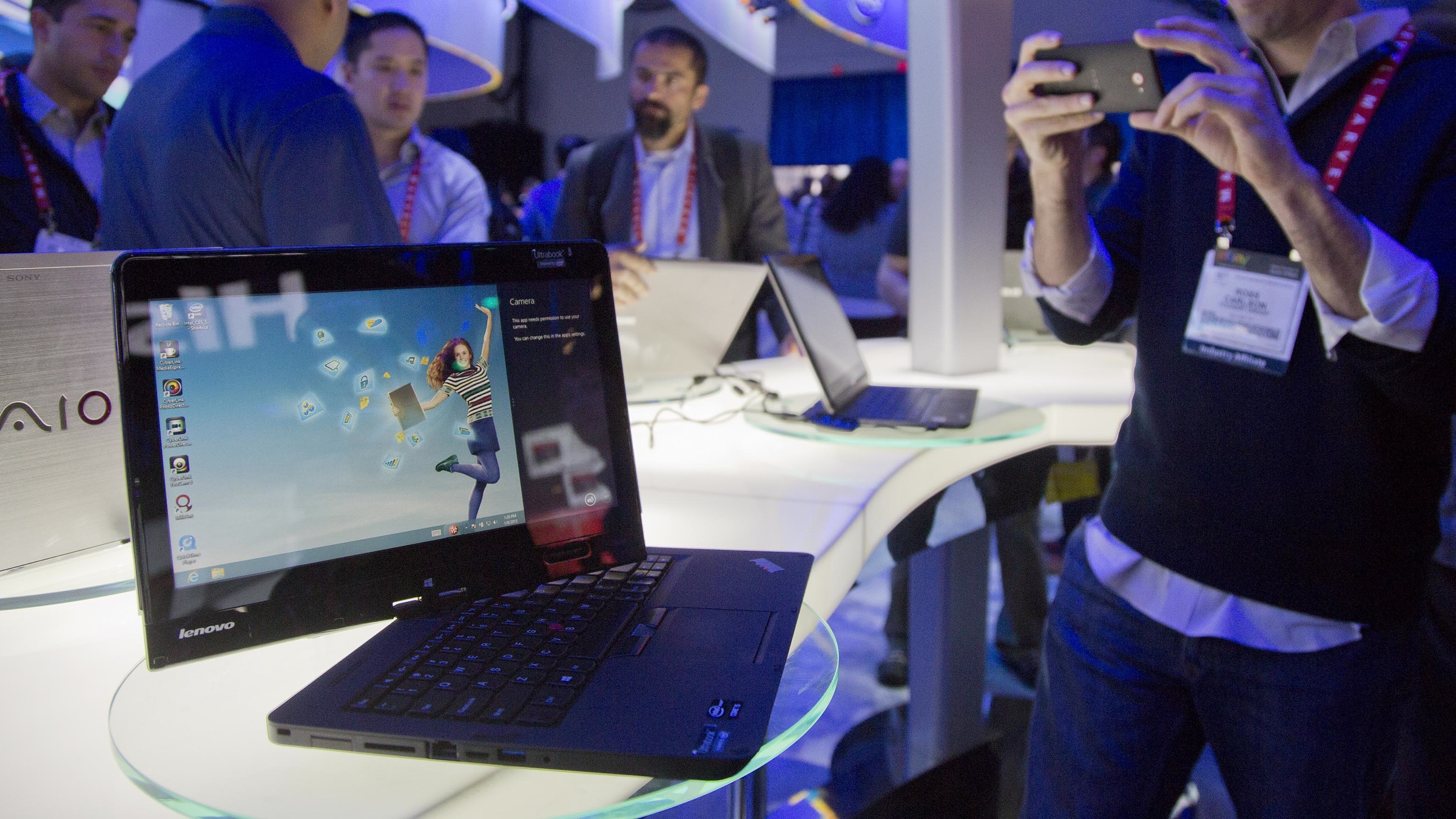 Convention goers photograph a Lenovo convertible Ultrabook at the Consumer Electronics Show, Tuesday, Jan. 8, 2013, in Las Vegas. The Ultrabook is a tablet that converts to a PC. (AP Photo/Julie Jacobson)