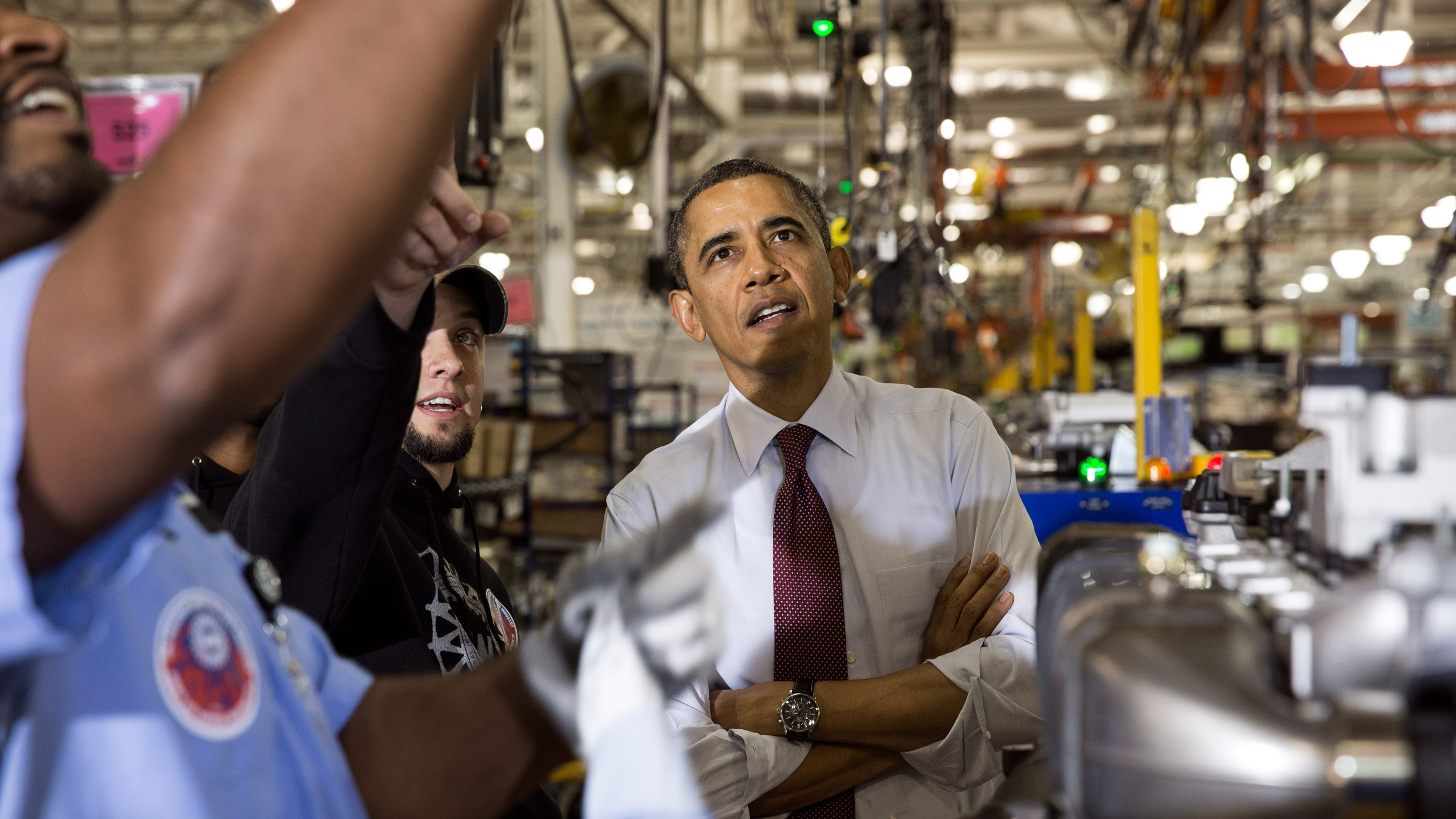 """President Barack Obama has a tour of the Daimler Detroit Diesel Facility in Redford, Michigan, Dec. 10, 2012. Tour guides are: Jeff Allen, Detroit Diesel, VP of Operations & Plant Manager; Mark """"Gibby"""" Gibson, UAW – NW Local 163 DCC Shop Chairperson (Engine Group). Station Three – Turbo Install: Four workers and a supervisor explain the process undertaken here."""