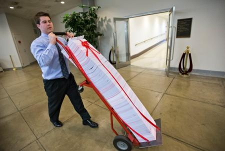 "A Senate aide delivers a stack of documents bound in red tape being used as a prop during debate on the budget in the Senate, at the Capitol in Washington, Friday, March 22, 2013. The paperwork was described as the federal regulations dealing with the Affordable Care Act, often called ""Obamacare."""