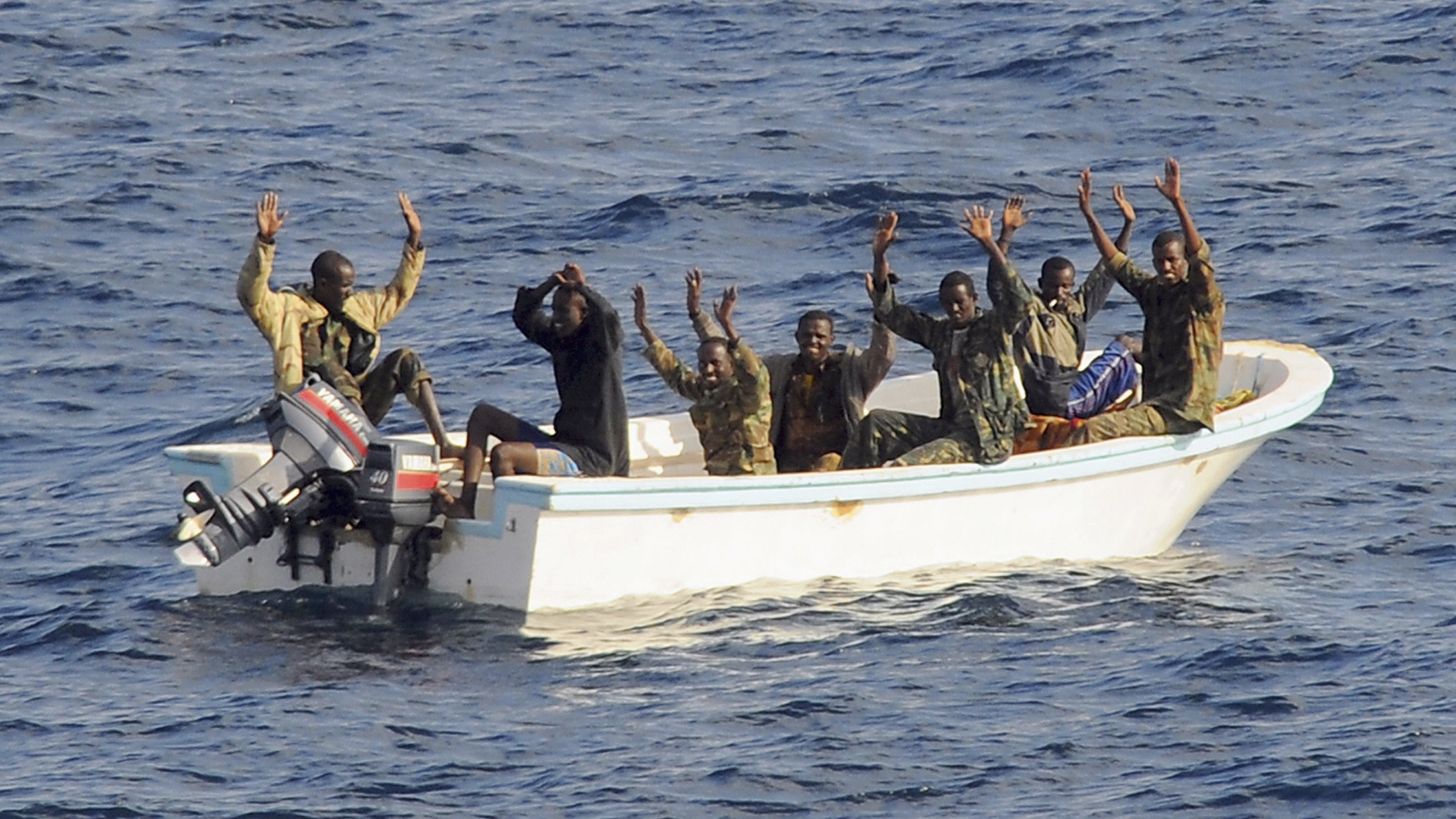 Suspected pirates keep their hands in the air as directed by sailors aboard the guided-missile cruiser USS Vella Gulf (CG 72) (not shown), in the Gulf of Aden, February 11, 2009. A multinational naval force seized the seven suspected pirates in the first such action in its anti-piracy campaign, the U.S. Navy said. REUTERS/Jason R. Zalasky/U.S. Navy/Handout (SOMALIA).  FOR EDITORIAL USE ONLY. NOT FOR SALE FOR MARKETING OR ADVERTISING CAMPAIGNS. - RTXBIUW