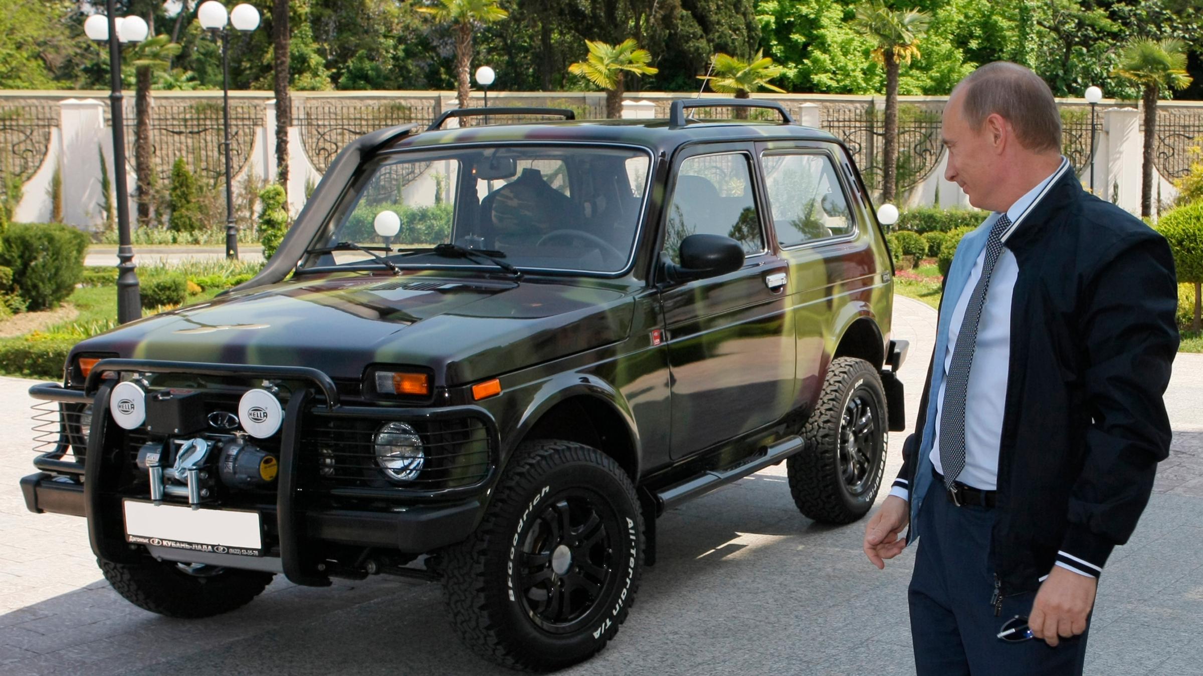 Vladimir Putin staring at an SUV