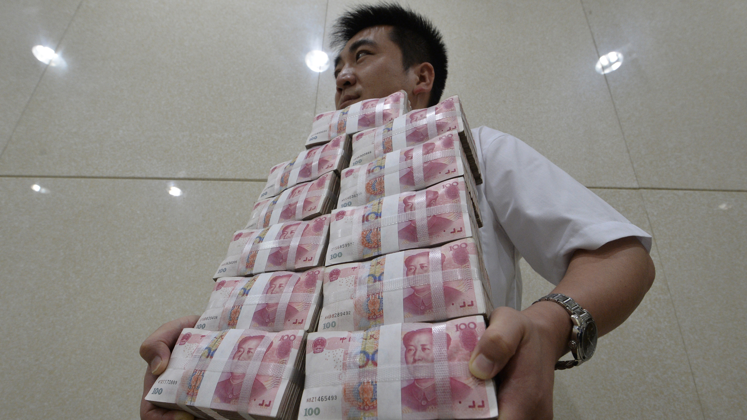 DATE IMPORTED:July 8, 2013An employee carries bundles of 100 yuan Chinese bank notes to store after counting at a bank in Taiyuan, Shanxi province July 4, 2013. Chinese authorities allowed short-term borrowing costs to spike to record levels on June 20, sending a blunt but effective message to banks that it was determined to bring risky credit growth under control. The crackdown, however, has only increased China Inc's reliance on shadow banking and its various components, underscoring the system's importance as China's rigid financial industry maneuvers through an economic slowdown. Picture taken July 4, 2013. REUTERS/Jon Woo
