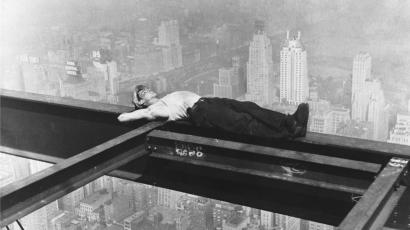 A workman takes a siesta on a girder during the building of Radio City.