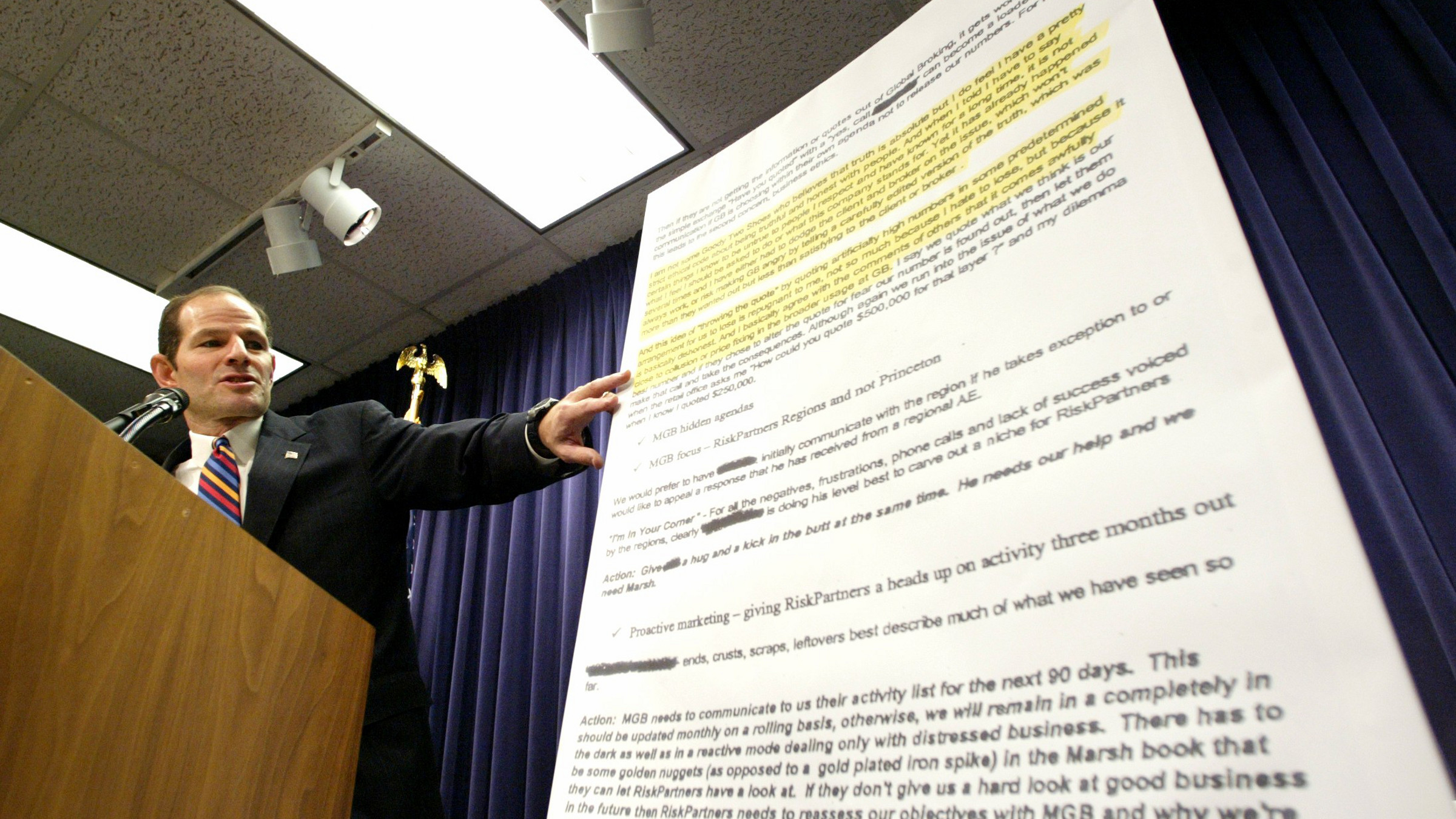 Attorney General Eliot Spitzer reads from a copy of emails from the insurance brokerage firm Marsh & McLennan Companies during a news conference in New York Thursday, Oct.14, 2004. Spitzer announced today he was suing the firm, and that his investigation revealed widespread corruption in the insurance industry.