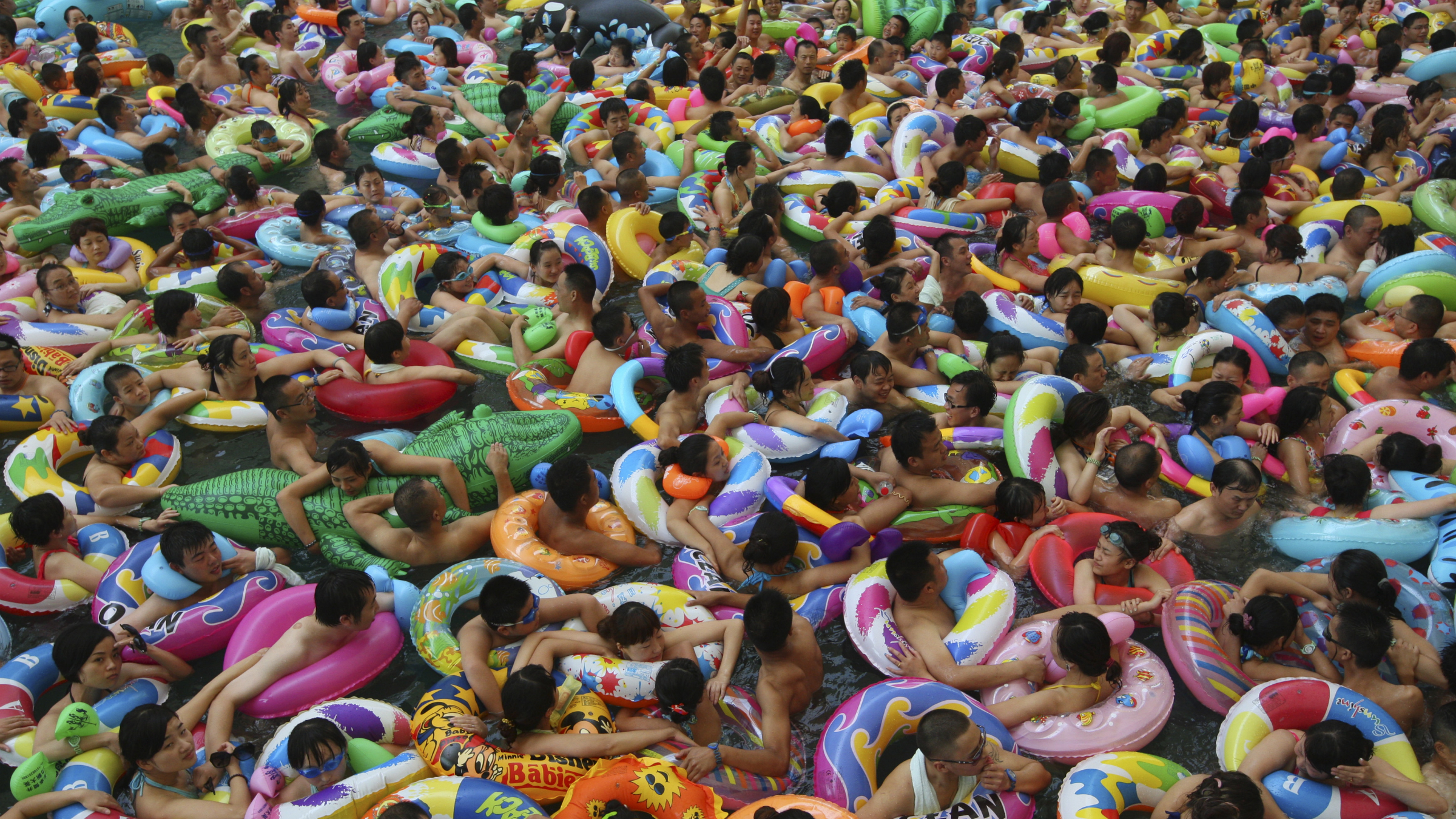 Visitors crowd an artificial wave pool at a tourist resort to escape the summer heat in Daying county of Suining, Sichuan province, July 27, 2013. Picture taken July 27, 2013. REUTERS/China Daily