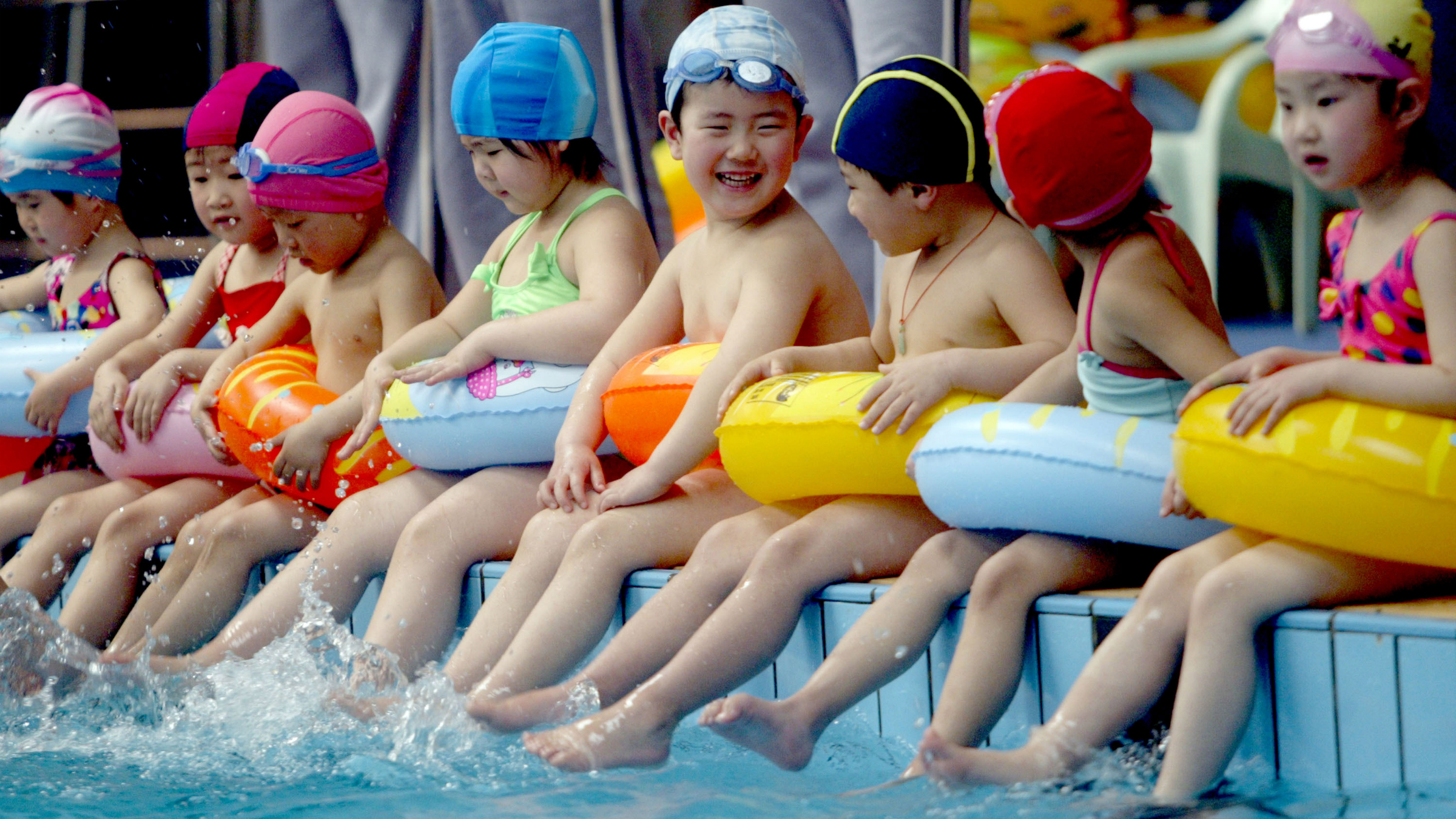 In this photo released by China's Xinhua News Agency, children sit along a pool as they take part in a swimming lesson, at the Natatorium of Shenyang, capital of northeast China's Liaoning Province, Monday, April 16, 2007. Youngsters from three to six are offered free swimming lessons at the natatorium. (AP Photo/Xinhua, Zhang Wenkui