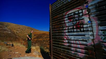 US Border Patrol agent Jerry Conlin looks along the old border wall along the US - Mexico border Thursday, June 13, 2013, where it ends at the base of a hill in San Diego. Illegal immigration into the United States would decrease by only 25 percent under a far-reaching Senate immigration bill, according to a recent analysis by the Congressional Budget Office.