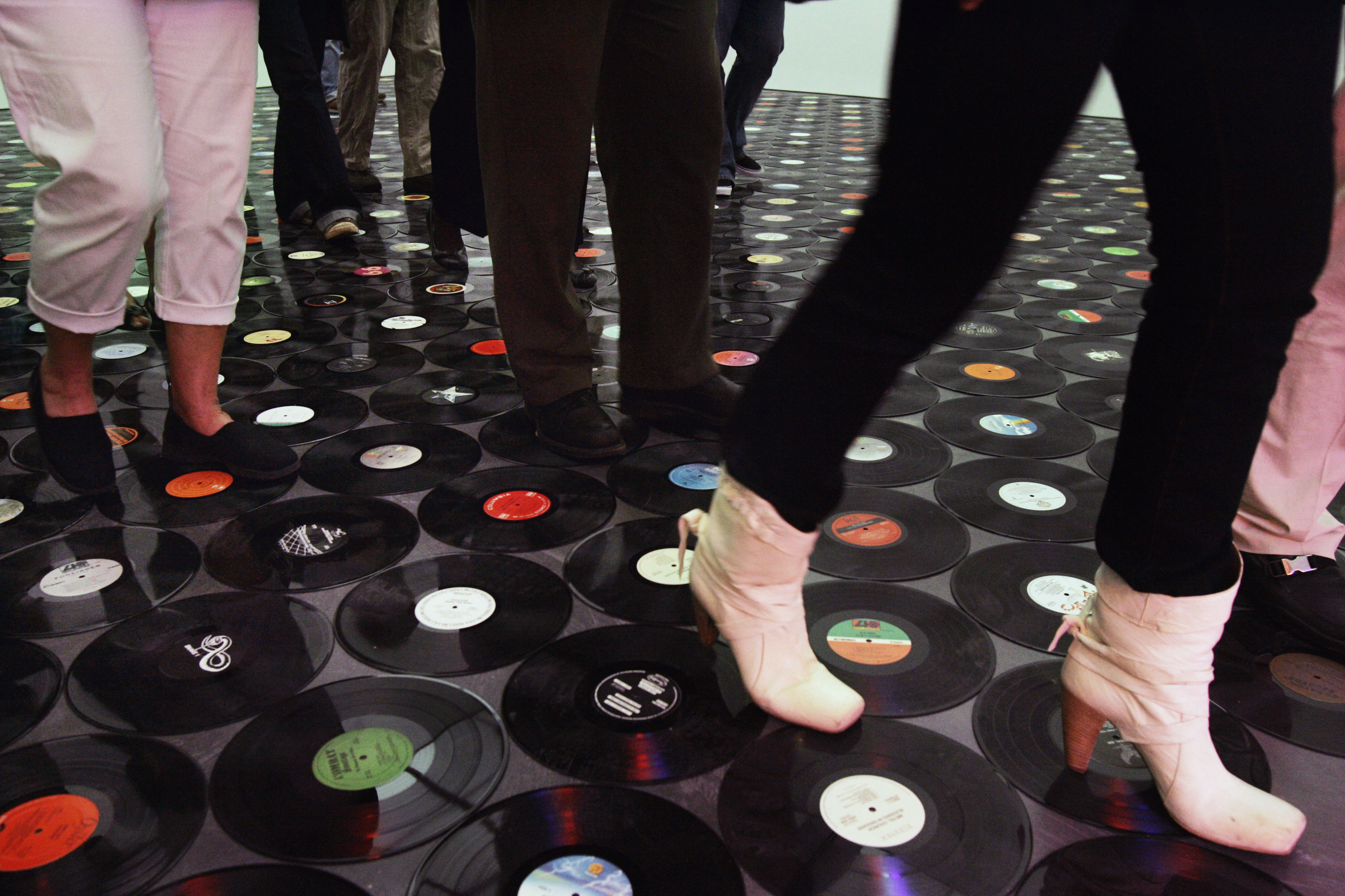 "Visitors to the Museum of Contemporary Art walk over a floor created by artist Christian Marclay made up of vinyl records Friday, Sept. 28, 2007, at the Museum of Contemporary Art in Chicago. The exhibit, part of ""Sympathy for the Devil: Art and Rock and Roll Since 1967,"" seeks to examine the ways that contemporary art and rock music have converged over the past 40 years, opens Saturday and runs through Jan. 6, 2008. (AP Photo/Charles Rex Arbogast)"