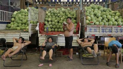 Vendors rest in front of trucks stacked with watermelons as they wait for their customers at a wholesale fruit and vegetable market in Wuhan, Hubei province July 6, 2012. China's annual consumer price inflation in June likely eased to a 29-month low with producer prices falling for the fourth month in a row, giving Beijing more room to stimulate the economy to fight softening demand, a Reuters poll found on Thursday. REUTERS/Stringer