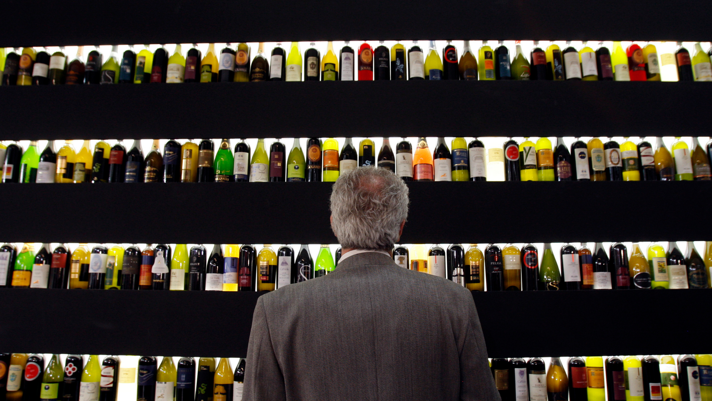 A man looks at bottles of wine on display.