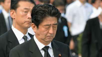 Japan's Prime Minister Shinzo Abe (C) offers silent prayers for victims of the 1945 atomic bombing, in the Peace Memorial Park in Hiroshima August 6, 2013, on the 68th anniversary of the world's first atomic bombing on the city. Mandatory Credit. REUTERS/Kyodo