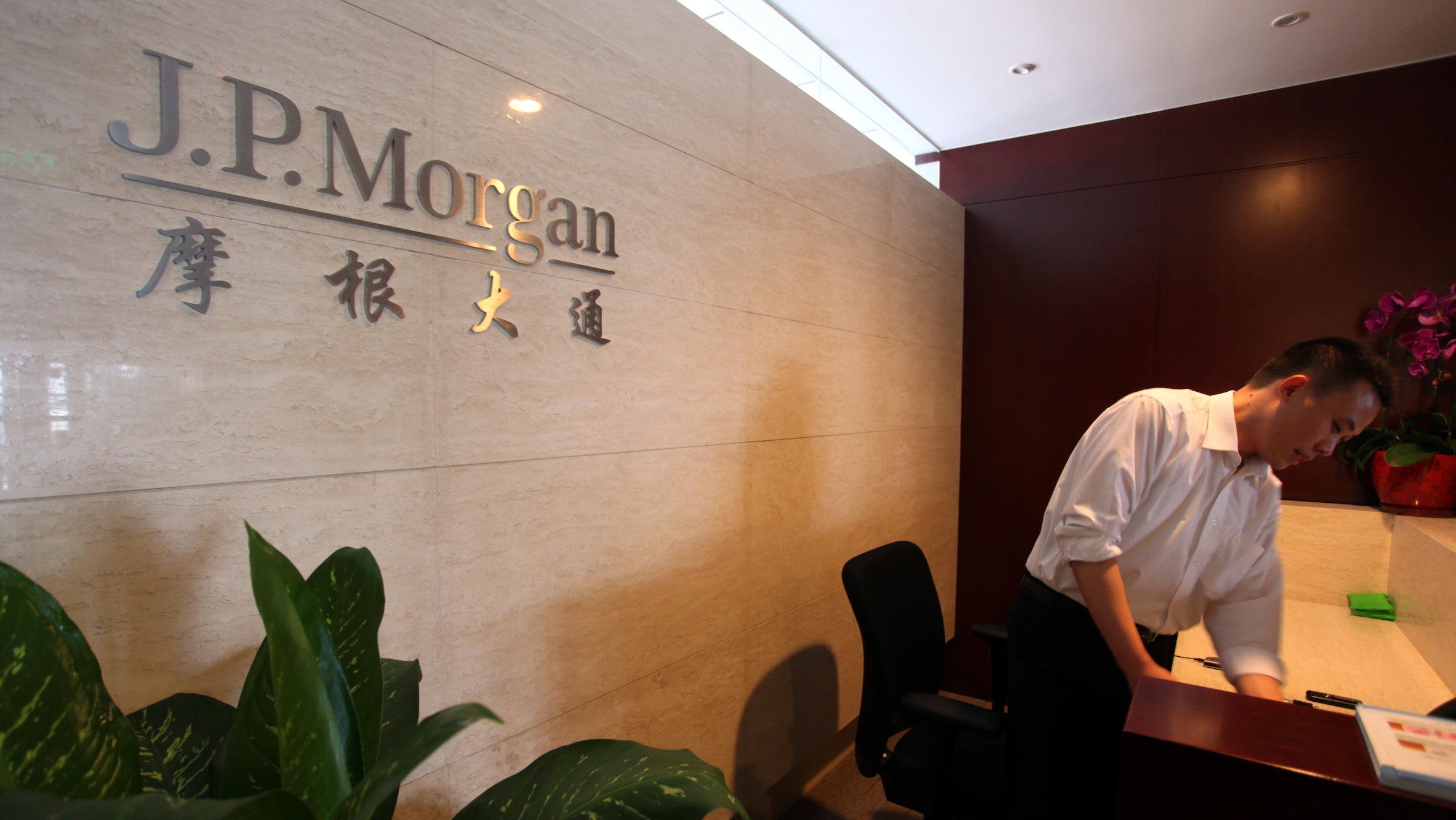 --FILE--A Chinese employee works at a branch of J.P.Morgan in Suzhou city, east Chinas Jiangsu province, 21 July 2012.  Federal authorities have opened a bribery investigation into whether JPMorgan Chase hired the children of powerful Chinese officials to help the bank win lucrative business in the booming nation, according to a confidential United States government document. The Hong Kong office of JPMorgan also hired the daughter of a Chinese railway official. That official was later detained on accusations of doling out government contracts in exchange for cash bribes, the government document and public records show. In May, according to a copy of the confidential government document, the S.E.C.s anti-bribery unit requested from JPMorgan a battery of records about Tang Xiaoning. He is the son of Tang Shuangning, who since 2007 has been chairman of the China Everbright Group. Before that, the elder Mr. Tang was the vice chairman of Chinas top banking regulator. The agency also inquired about JPMorgans hiring of Zhang Xixi, the daughter of the railway official Zhang Shuguang. Among other information, the S.E.C. sought documents sufficient to identify all persons involved in the decision to hire her.