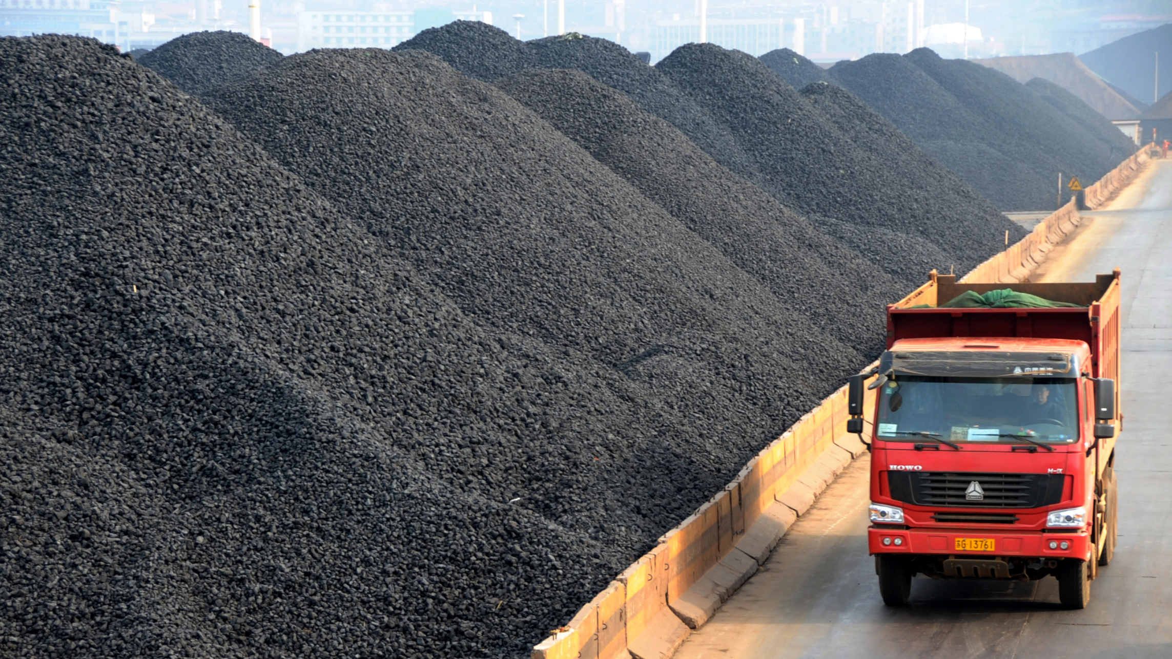 -A truck passes by piles of coal at a coalyard at the Port of Lianyungang in Lianyungang city, east Chinas Jiangsu province, 9 April 2011. China is expected to consume approximately 4 billion metric tons of coal in 2015, 700 million metric tons more than that of 2010, said Chen Qi, director of the regulating division at the China National Coal Association (CNCA). Chen added that about 300 million metric tons of coal reserves will be added this year.(Imaginechina via AP Images