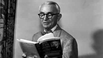 "Author Dale Carnegie reads his book ""How to Win Friends and Influence People."" in Chicago on July 7, 1955. Carnegie was at the National Convention of the Sale Carnegie Institute of Effective Speaking and Human Relations which was attended by 150 representatives who operate Carnegie public speaking classes throughout the world. It was one of his few public appearances. (AP Photo)"